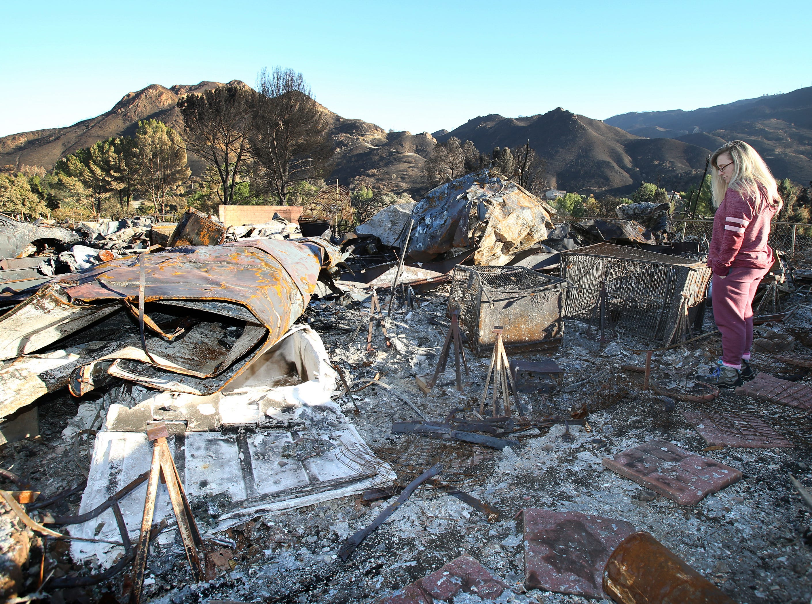 Rosanna DeVere looks out at what remains of her home, which was destroyed during the Woolsey Fire. In front of her are her two large bird cages that housed her cockatoo and cockatiel, which she did get out before the fire hit her property in the Seminole Springs Mobile Home Park in Agoura Hills.