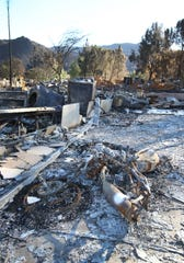 The charred remains of what used to be a motorcycle lies at one of the properties in the Seminole Springs Mobile Home Park, where many homes were destroyed by the Woolsey Fire.