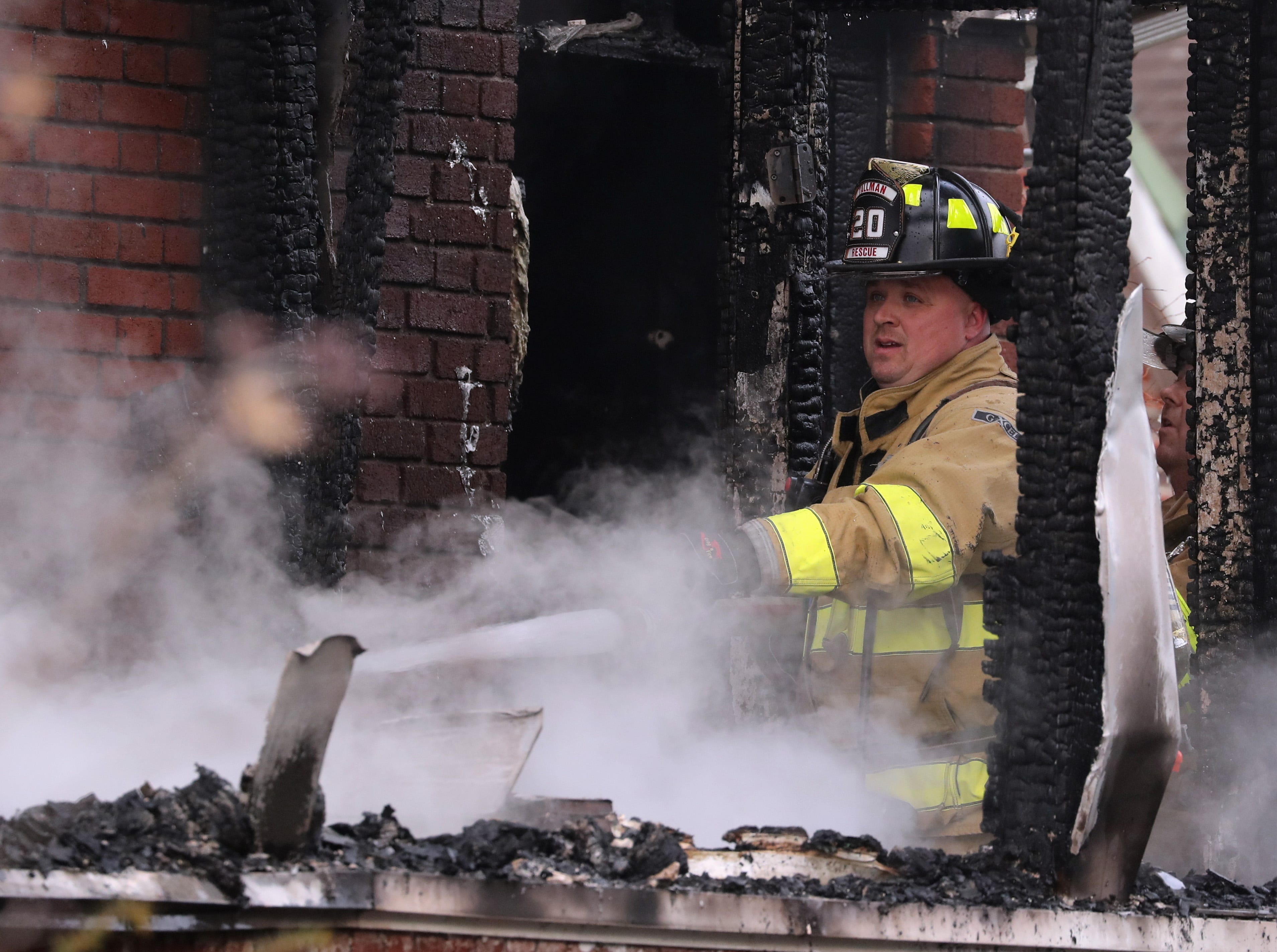 A Tallman Fire Dept. firefighter uses a hose on a house fire on Washington Ave. in Suffern Dec. 5, 2018.
