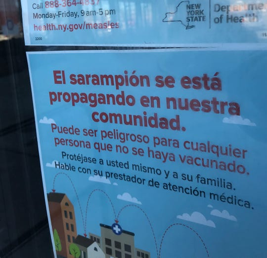 Warnings about measles in various languages, including Spanish, were posted near the entrance of Compare Foods grocery store in Spring Valley.
