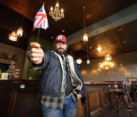 Chef/Owner David DiBari holds up the Union Jack flag inside his new restaurant, The Rare Bit, on Cedar Street in Dobbs Ferry, Dec. 5, 2018.