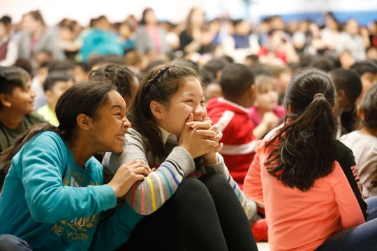 Elmwood Elementary School student Angie Ortiz, 11, from Spring Valley, center, is hugged by her friend Leah Caldwell, 11, who won a national writing contest through Story Pirates and Random House Kids which was announced at the school on Dec. 5, 2018.