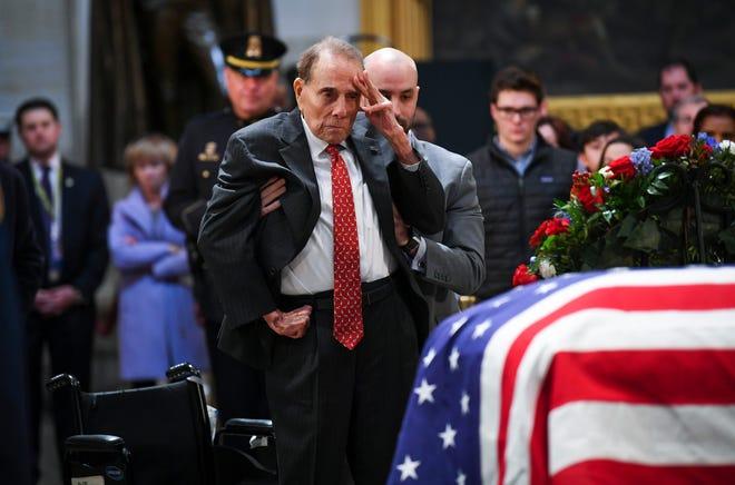 Former Sen. Bob Dole salutes the casket of former President George H.W. Bush on Dec. 4, 2018.