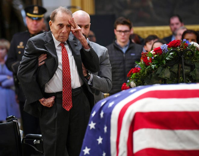 """Bob Dole saluted a fellow World War II veteran under the Capitol dome as he rose to honor George H.W. Bush on Dec. 4, 2018.  Dole, the 95-year-old former Senate majority leader, relied on an aide to help him stand on the floor of the Capitol rotunda before offering his gesture beside the casket of Bush, his onetime rival in the 1988 Republican presidential primary. Bush's spokesman, Jim McGrath, described the salute as """"a last, powerful gesture of respect from one member of the Greatest Generation, @SenatorDole, to another.""""Dole was among mourners filing into the rotunda to pay respects to Bush on day two of his lying in state, a day that also drew Colin Powell, his former Joint Chiefs of Staff chairman, and Sully, the yellow Labrador who worked as the former president's service dog."""