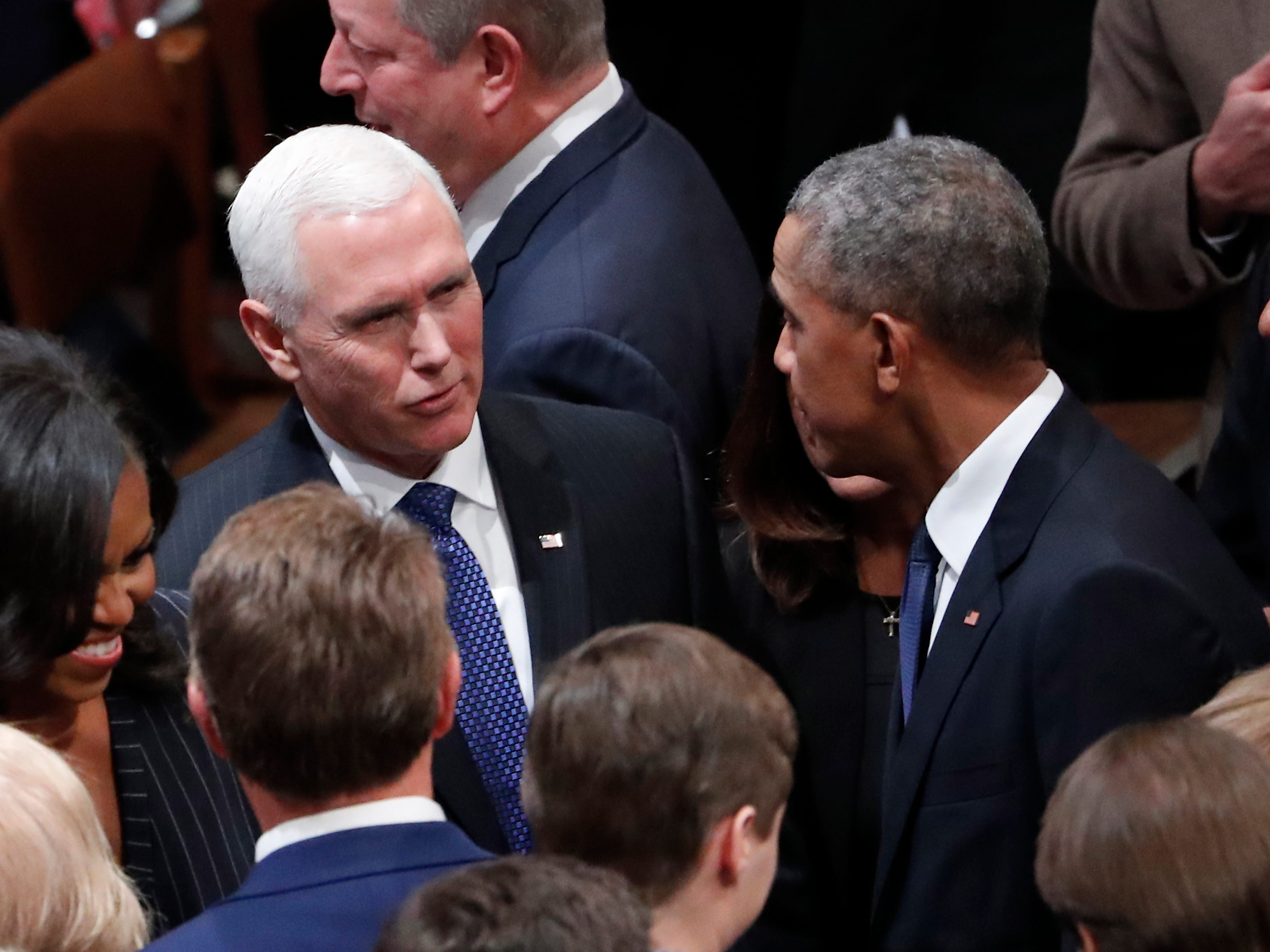 Former President Barack Obama, right, talks with Vice President Mike Pence before the funeral services for former President George H. W. Bush at the National Cathedral, in Washington, Dec. 5, 2018.