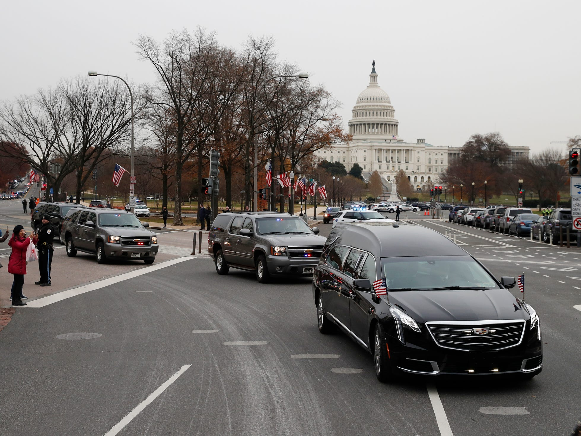The hearse carrying the flag-draped casket of former President George H.W. Bush is driven away from the Capitol to a State Funeral at the National Cathedral, Wednesday, Dec. 5, 2018, in Washington. (AP Photo/Alex Brandon, Pool) ORG XMIT: DCAB205