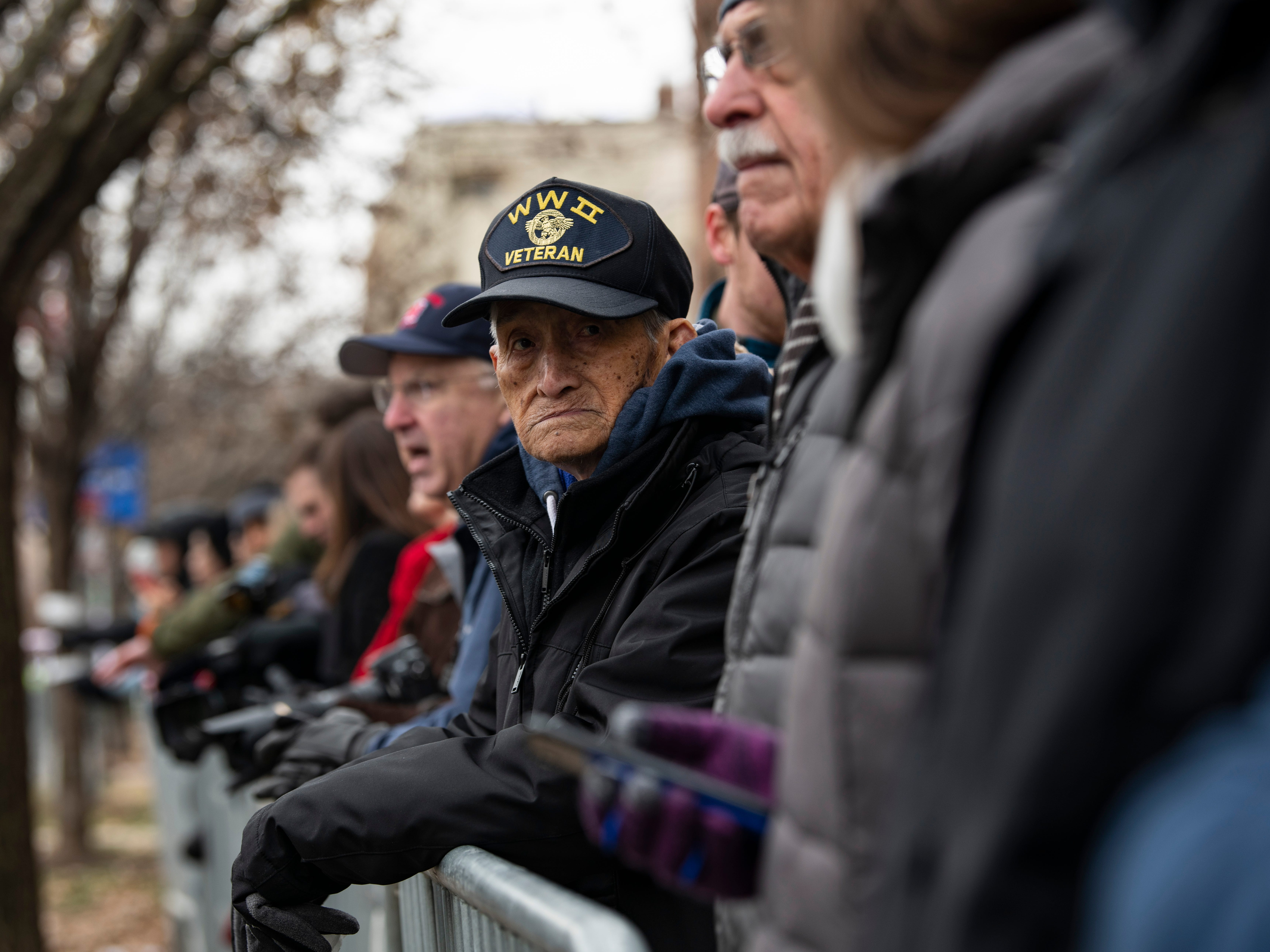 Justino Delara, 100-years-old, joins the crowd to watch the arrival of the hearse containing the flag-draped casket of former President George H.W. Bush at the Washington National Cathedral in Washington, Dec. 5, 2018.