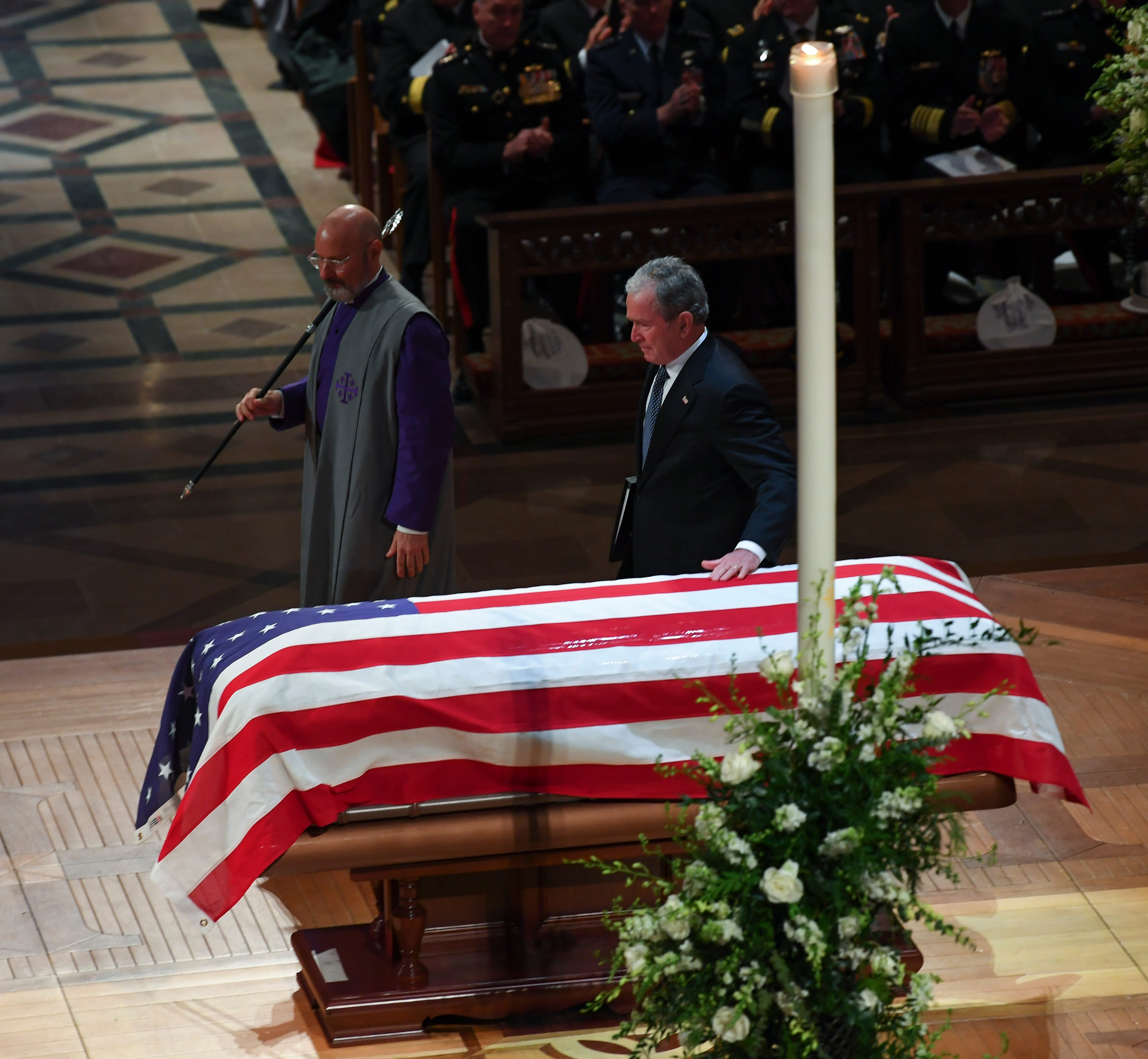 Former President George W. Bush touches his father's casket after speaking about him during the former president's state funeral at the Washington National Cathedral.