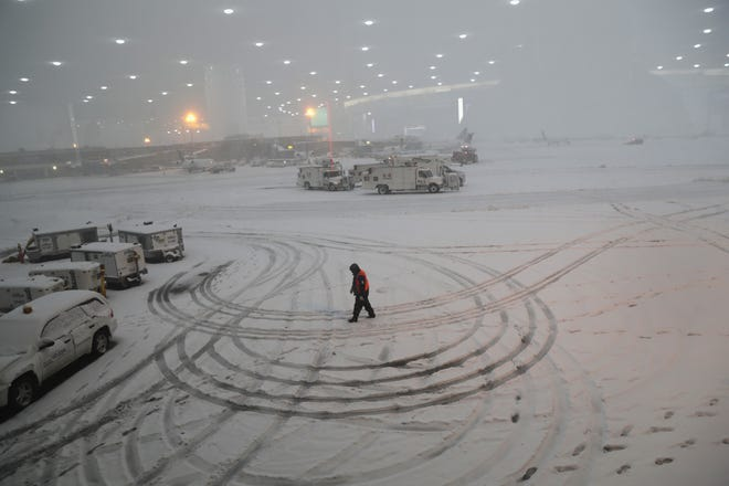 A ground crew member walks through the snow at the Newark Liberty International Airport on November 15, 2018 in Newark, New Jersey.