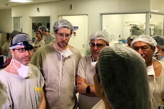 In this Dec. 15, 2017 photo provided by transplant surgeon Dr. Wellington Andraus, left with magnifying glasses, he and Dr. Dani Ejzenberg, second left, confer with colleagues at the Hospital das Clinicas of the University of Sao Paulo School of Medicine, Sao Paulo, Brazil, on the day of the birth of the baby girl born to a woman with a uterus transplanted from a deceased donor.