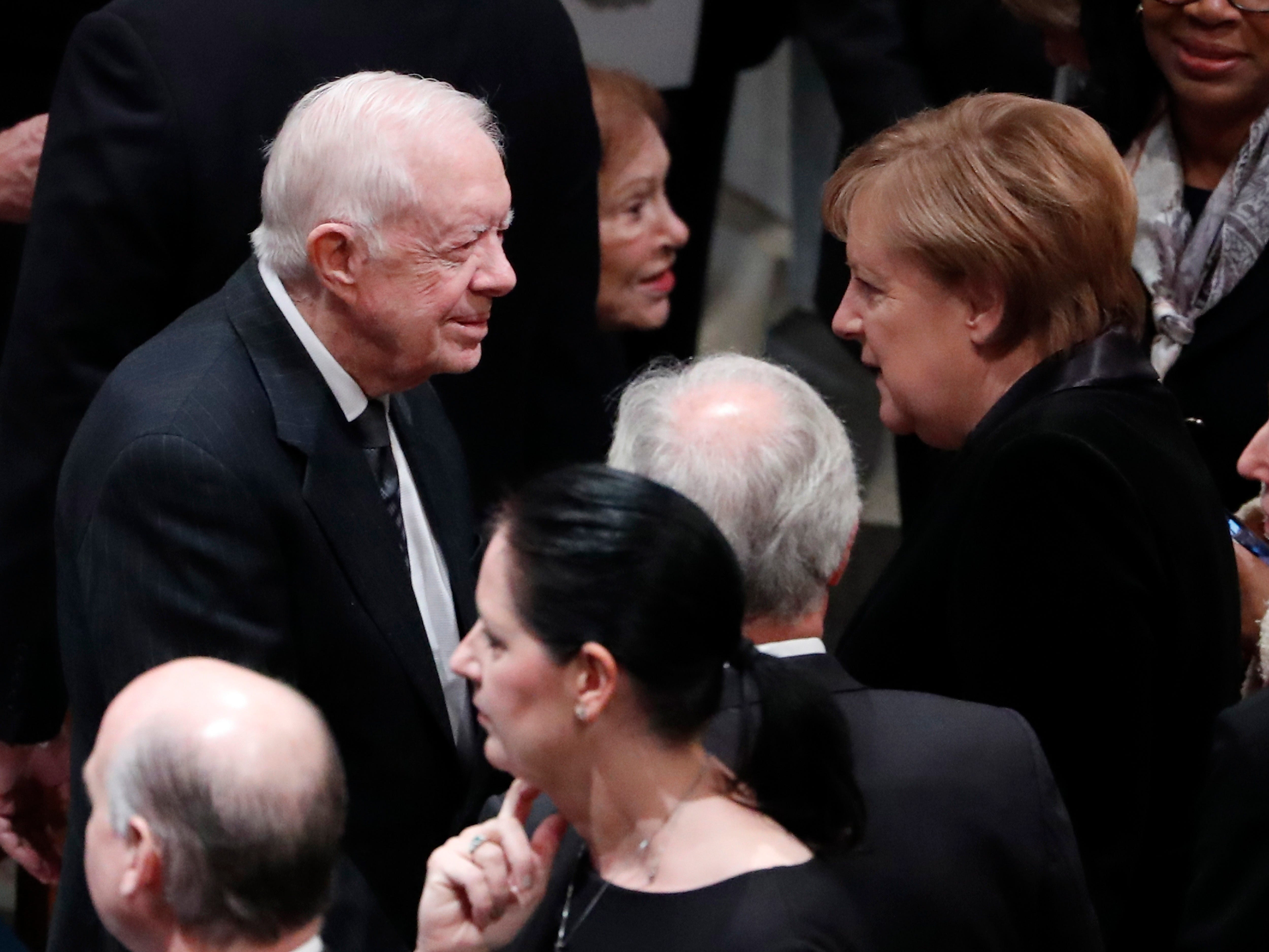 Former President Jimmy Carter, left, talks with German Chancellor Angela Merkel as they arrive for the funeral services for former President George H. W. Bush at the National Cathedral, in Washington, Dec. 5, 2018.