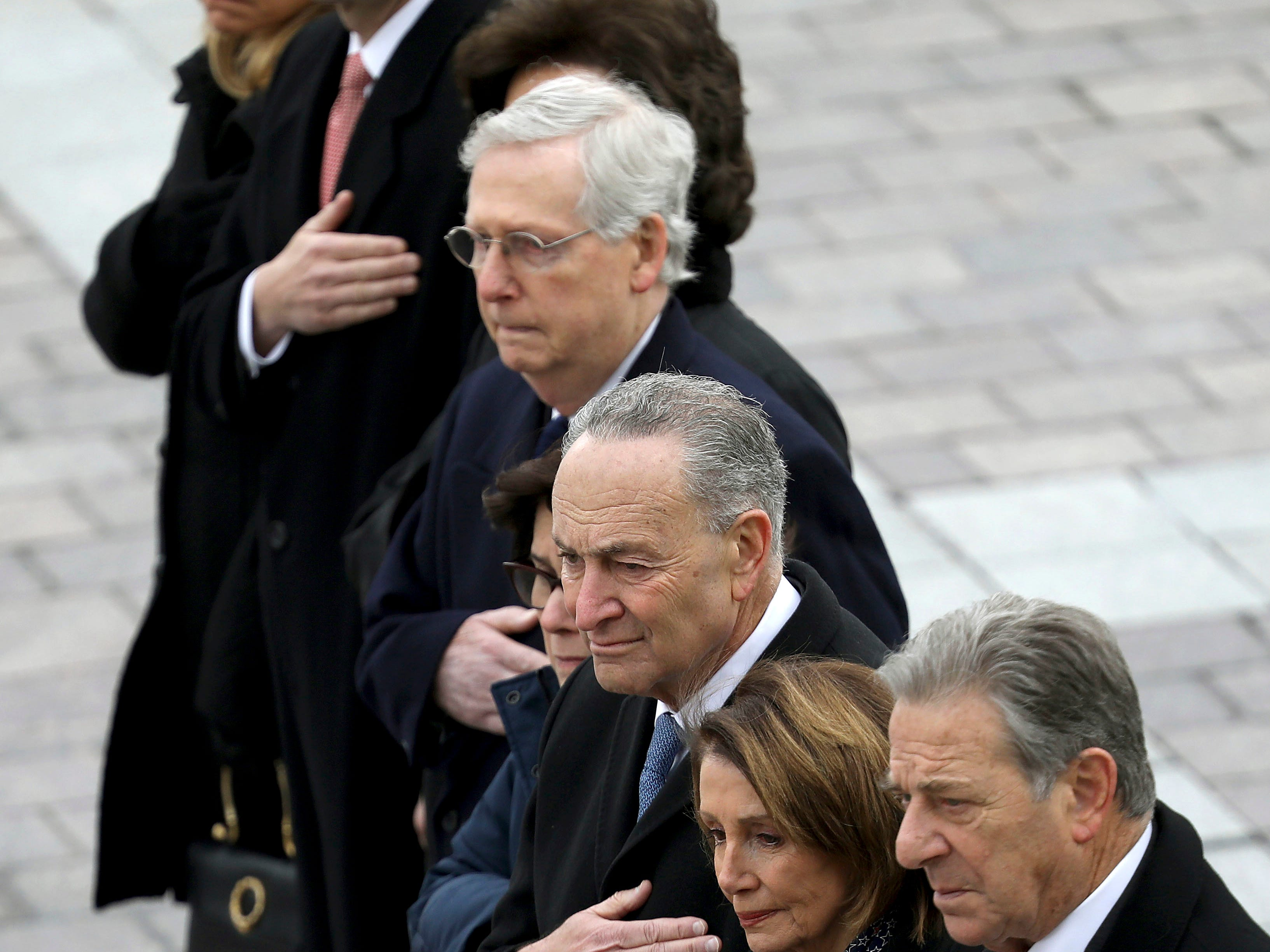 Congressional leaders from left to right, Speaker of the House Paul Ryan, R-Wis, Senate Majority Leader Mitch McConnell, R-Ky., Senate Minority Leader Chuck Schumer, D-NY, and House Minority Leader Nancy Pelosi, D-Calif., watch as a U.S. military honor guard carries the flag-draped casket of former U.S. President George H. W. Bush from the U.S. Capitol Wednesday, Dec. 5, 2018, in Washington.
