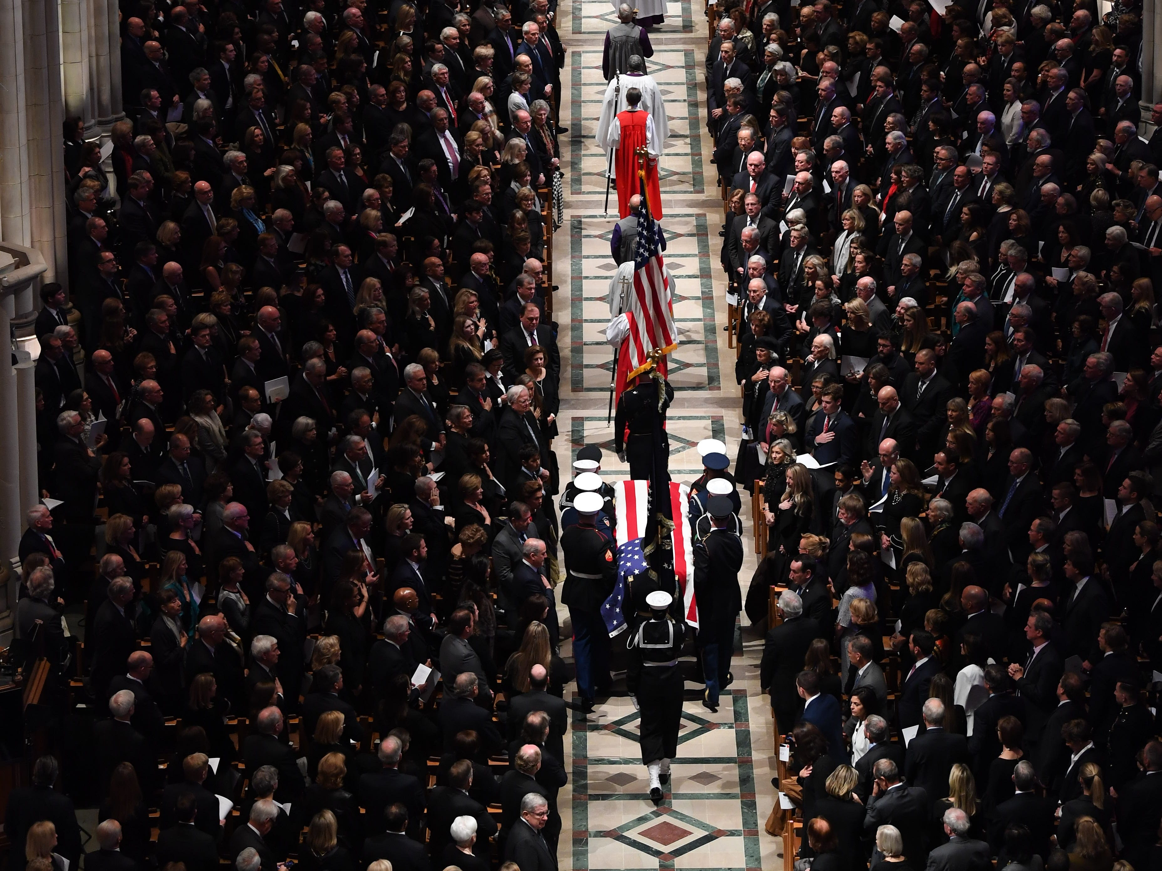 The flag-draped casket of former President George H.W. Bush is carried by a military honor guard during a State Funeral at the National Cathedral, Wednesday, Dec. 5, 2018, in Washington.