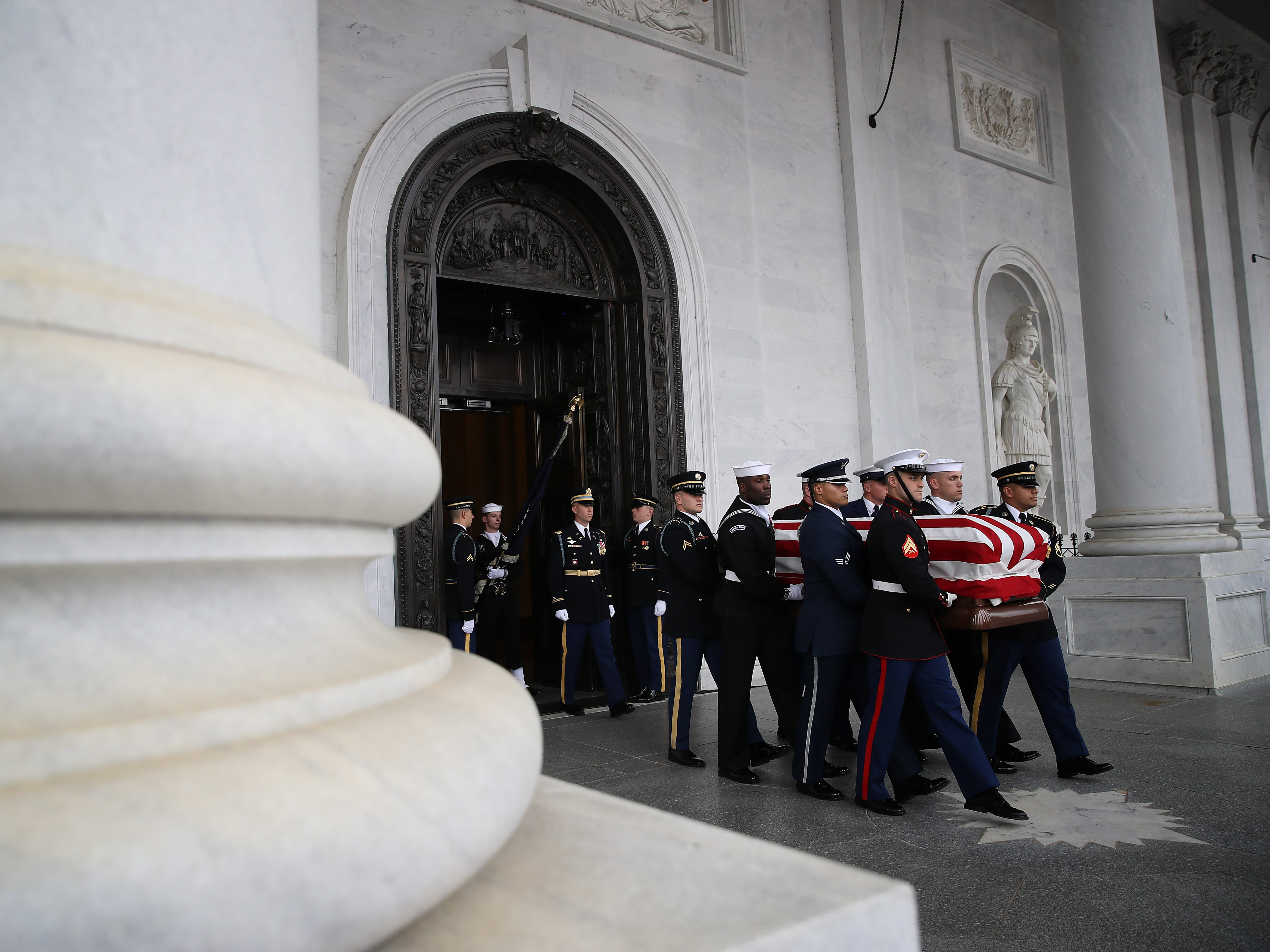 A U.S. military honor guard team carries the flag draped casket of former President George H.W. Bush from the U.S. Capitol, Dec. 5, 2018, in Washington.