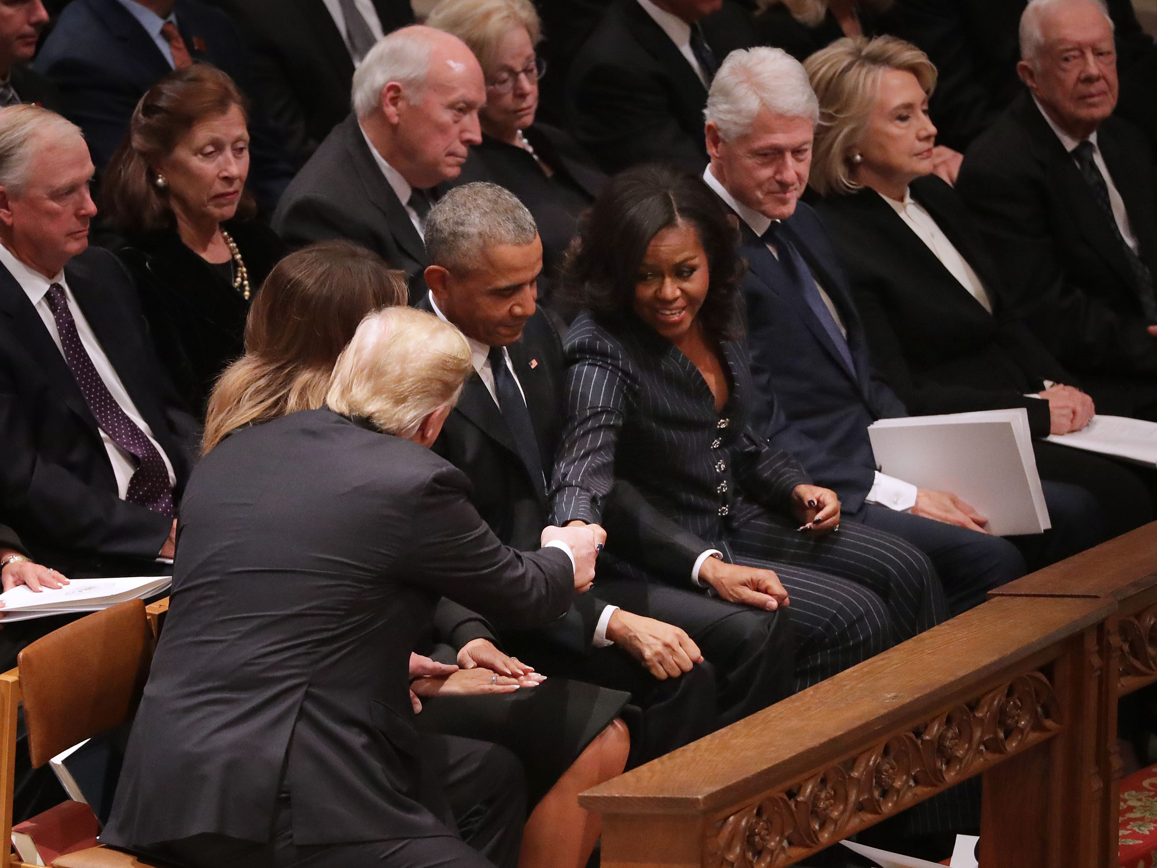 President Donald Trump and first lady Melania Trump greet former President Barack Obama and Michelle Obama as they join other former presidents and vice presidents and their spouses for the state funeral for former President George H.W. Bush at the National Cathedral, Dec. 5, 2018, in Washington.