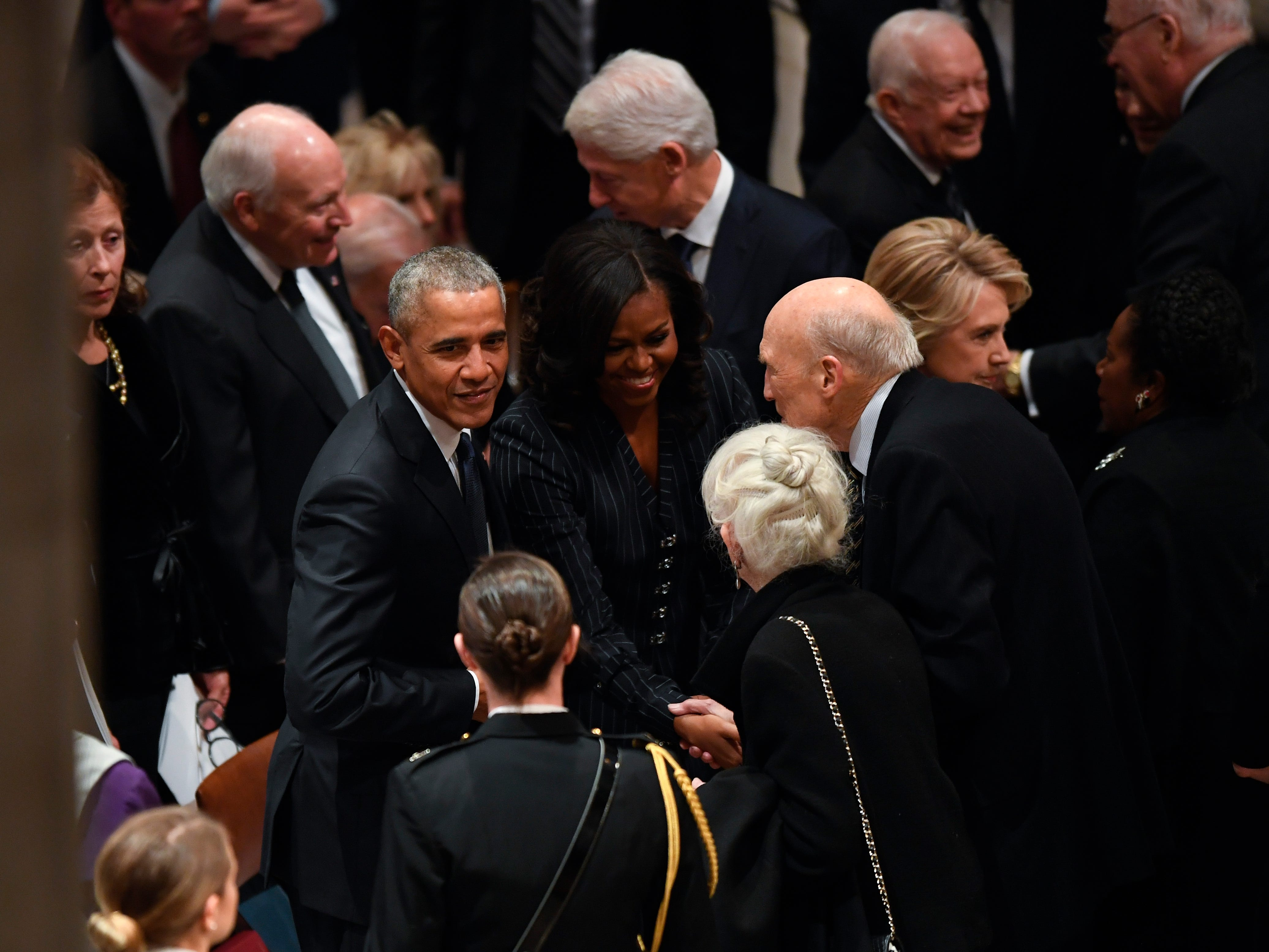 Former President Barack Obama and his wife, Michelle Obama, greet former Sen. Alan Simpson as former President George H.W. Bush before a state funeral at the Washington National Cathedral in Washington, Dec. 5, 2018.