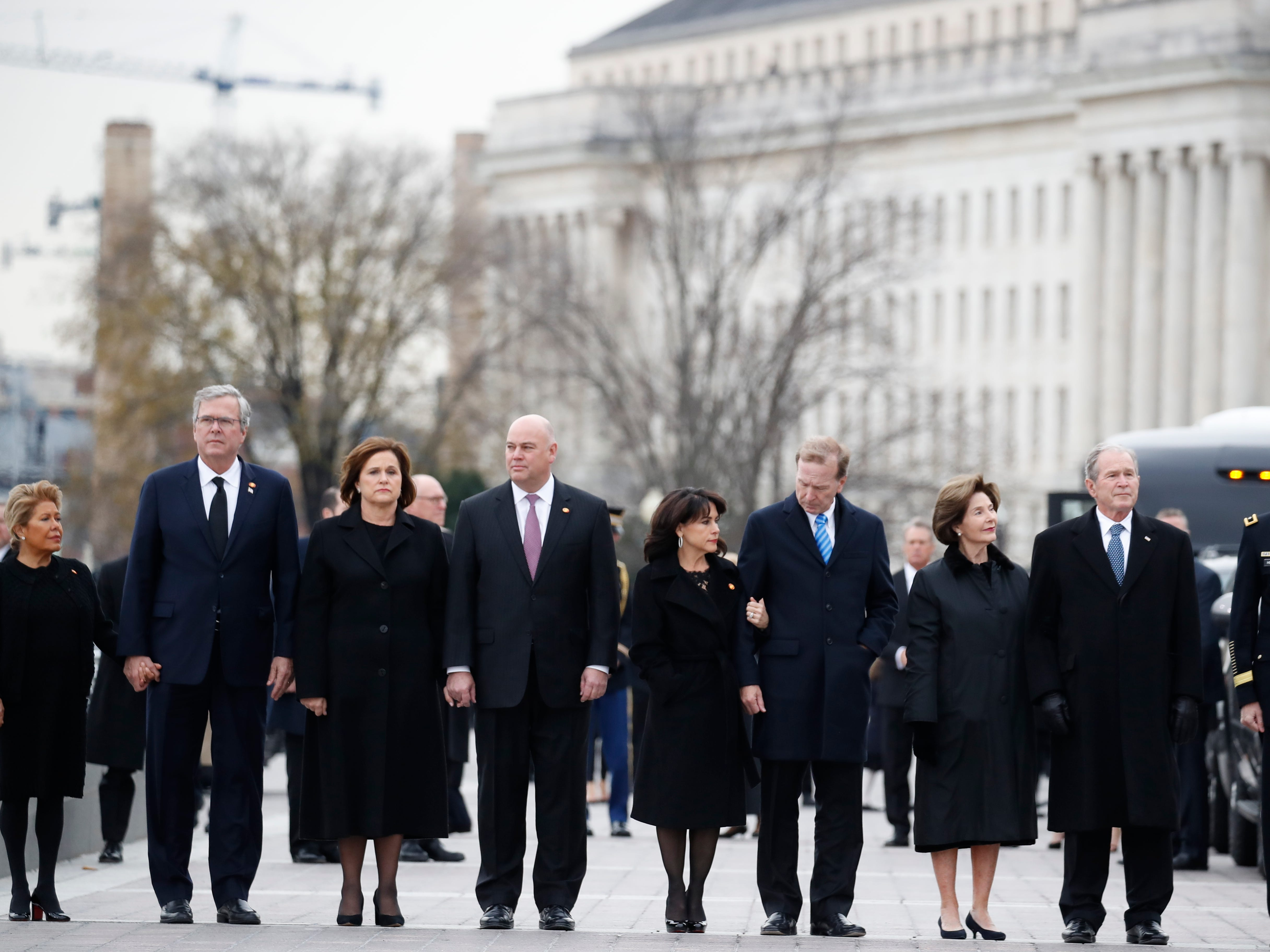From right, former President George W. Bush, second from right, former first lady Laura Bush, Neil Bush, Sharon Bush, Bobby Koch, Doro Koch, Jeb Bush and Columba Bush, stand just prior to the flag-draped casket of former President George H.W. Bush being carried by a joint services military honor guard from the U.S. Capitol, Wednesday, Dec. 5, 2018, in Washington.
