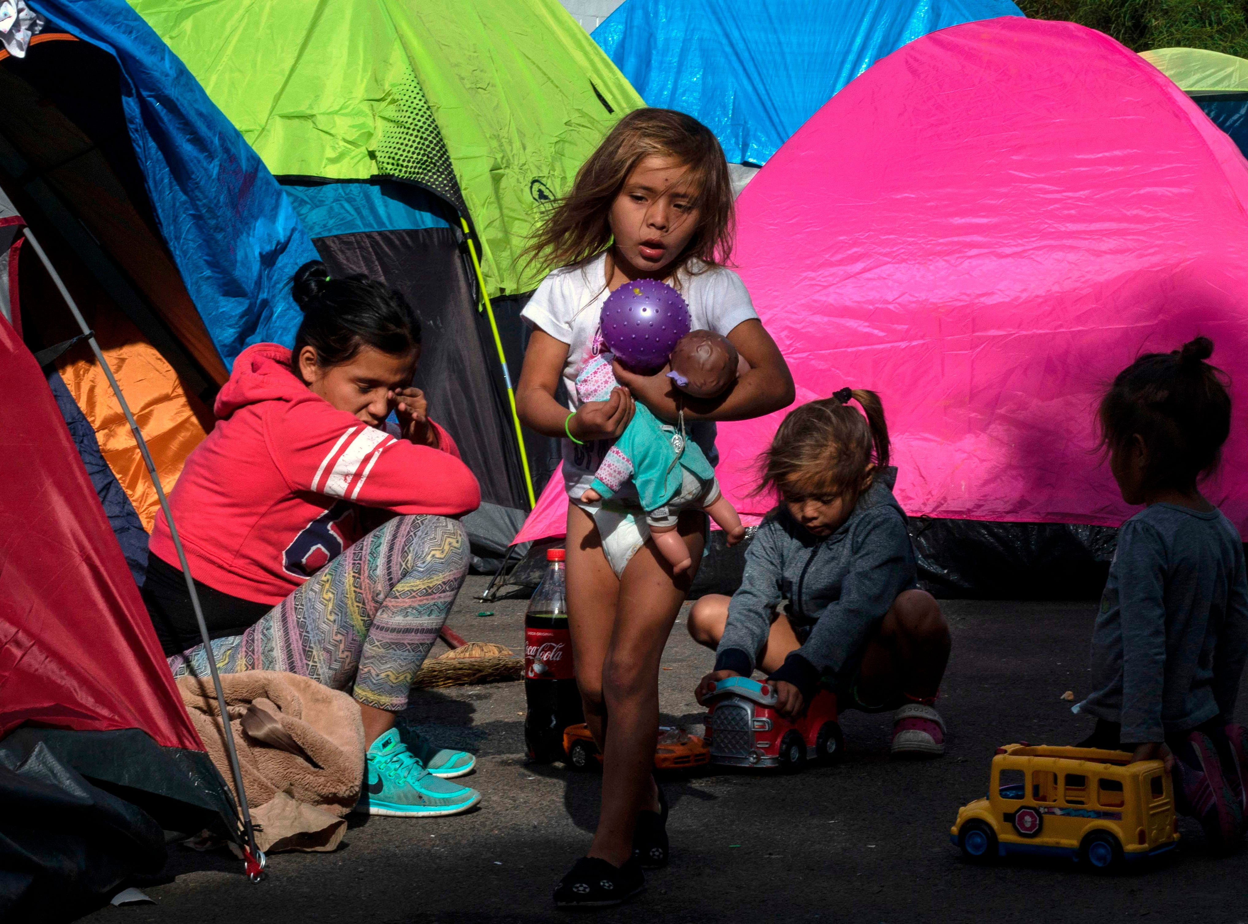 Children part of the Central American migrants caravan, play on the street, while camping near a closed temporary shelter a few meters from the US-Mexico border in Tijuana, Baja California State, Mexico, Dec. 4, 2018. Thousands of Central American migrants, mostly Hondurans, have trekked for over a month in the hopes of reaching the United States.