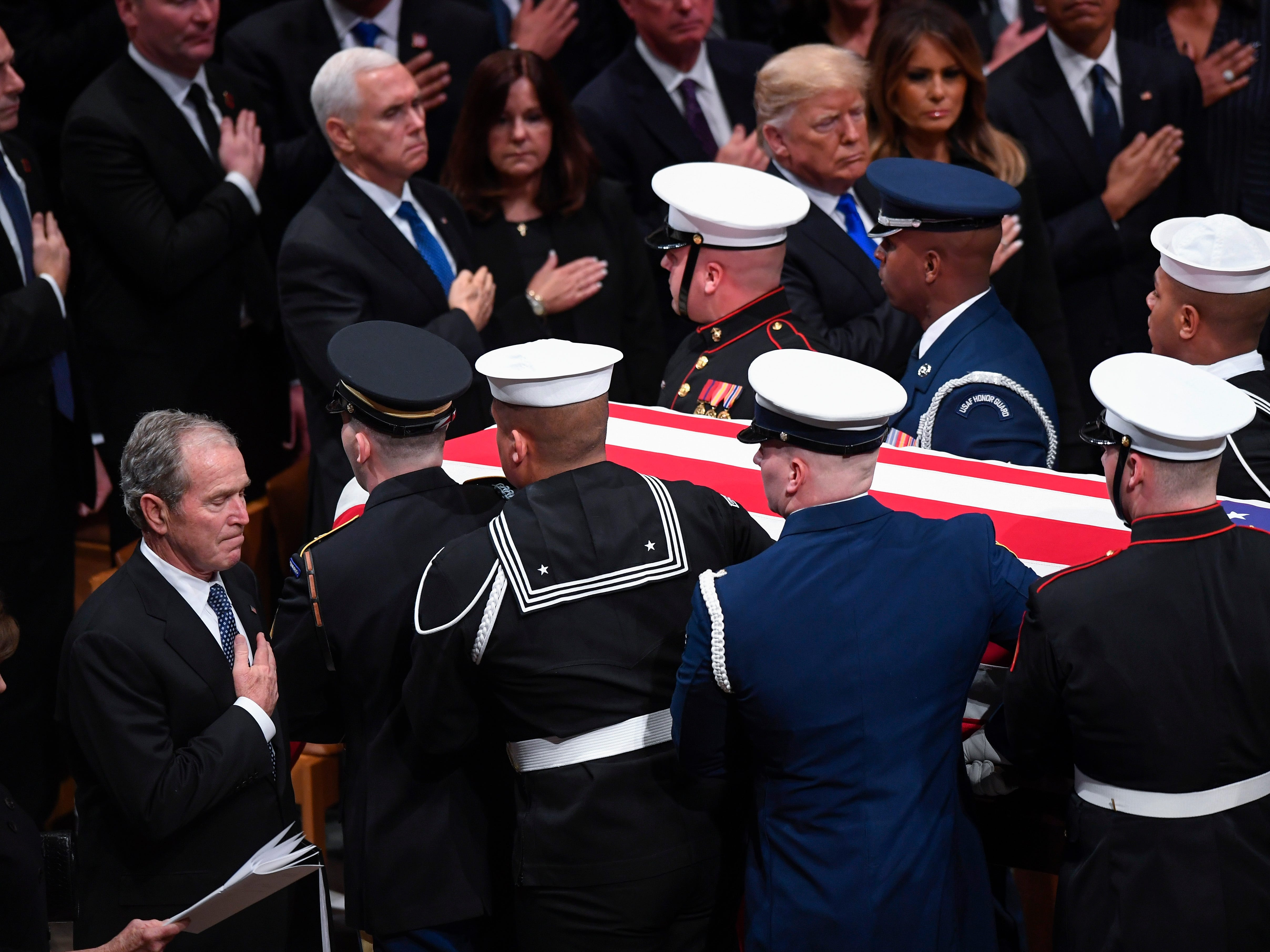 Former President George W. Bush, with hand on heart, stands as his father, former President George H.W. Bush is carried from the Washington National Cathedral at the conclusion of the State Funeral service on Dec. 5, 2018.