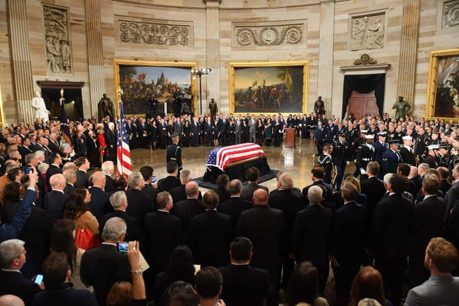 """President George H.W. Bush lies in state at the U.S. Capitol Rotunda on Dec.3, 2018, he is wearing a pair of socks that """"pay tribute to his lifetime of service,"""" family spokesman Jim McGrath said. Bush was long known for wearing colorful, often whimsical socks. Days before the Texas primary in March, he wore red, white and blue socks emblazoned with the word """"VOTE."""" He wore book-themed socks to his wife Barbara's funeral in April to celebrate her commitment to literacy."""