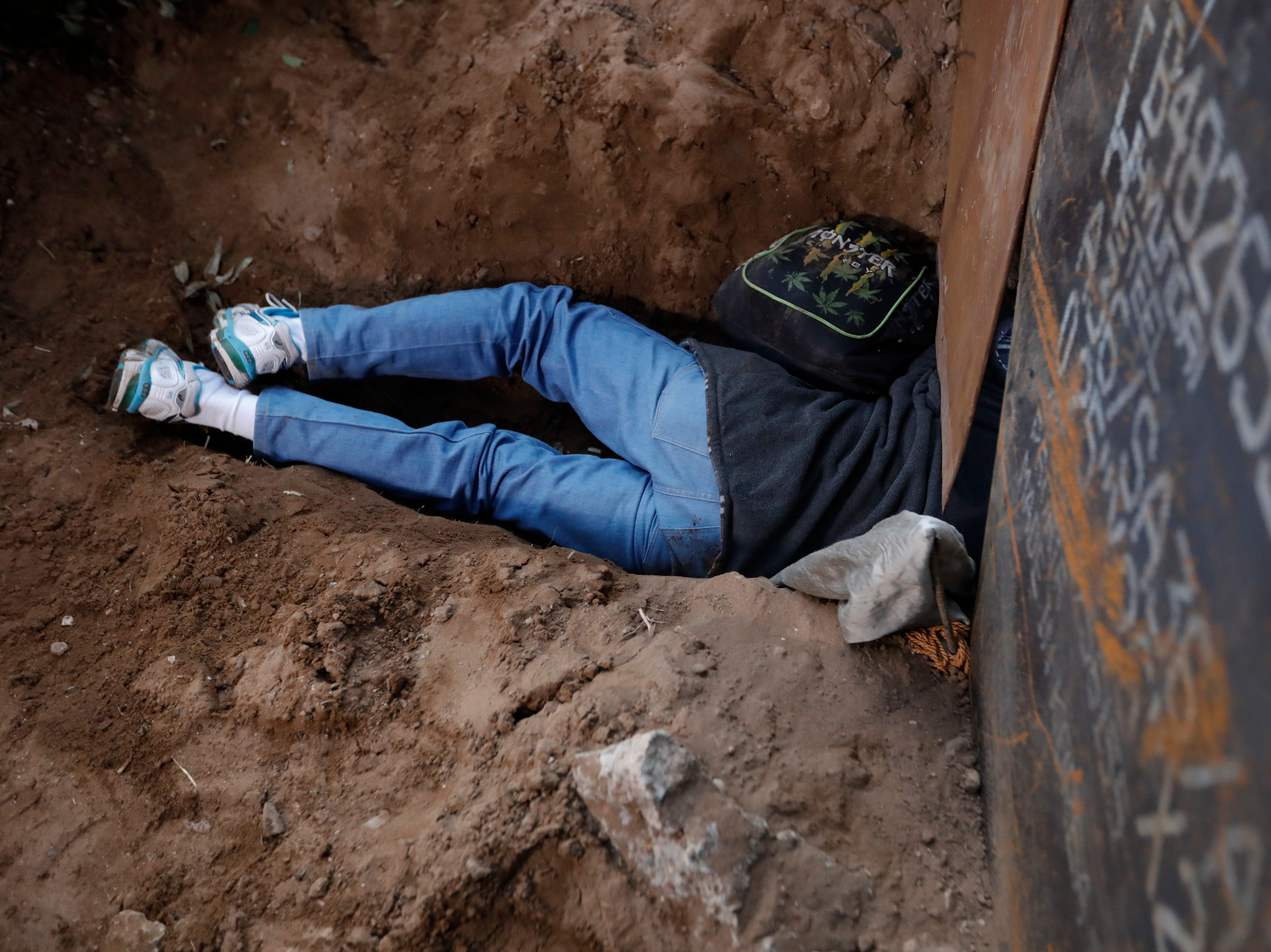 A Honduran migrant crawls through a hole under the U.S. border fence in Playas de Tijuana, Mexico, Tuesday, Dec. 4, 2018. Discouraged by the long wait to apply for asylum through official ports of entry, many Central American migrants from recent caravans are choosing to cross the U.S. border wall and hand themselves in to border patrol agents.