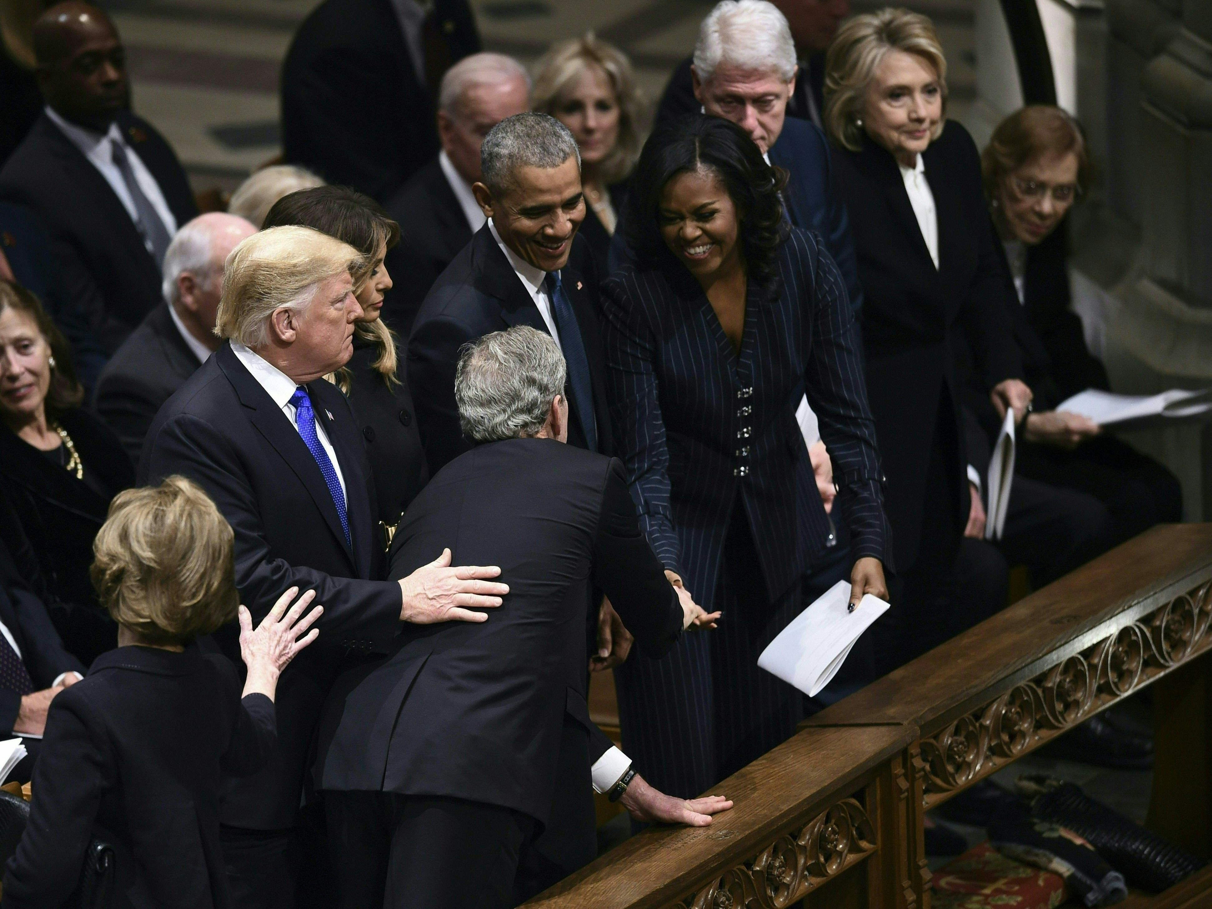 Former president George W. Bush, center, reaches past President Donald Trump, First Lady Melania Trump and former president Barack Obama to greet former first Lady Michelle Obama during the funeral service of former President George H.W. Bush at the National Cathedral in Washington, Dec. 5, 2018.
