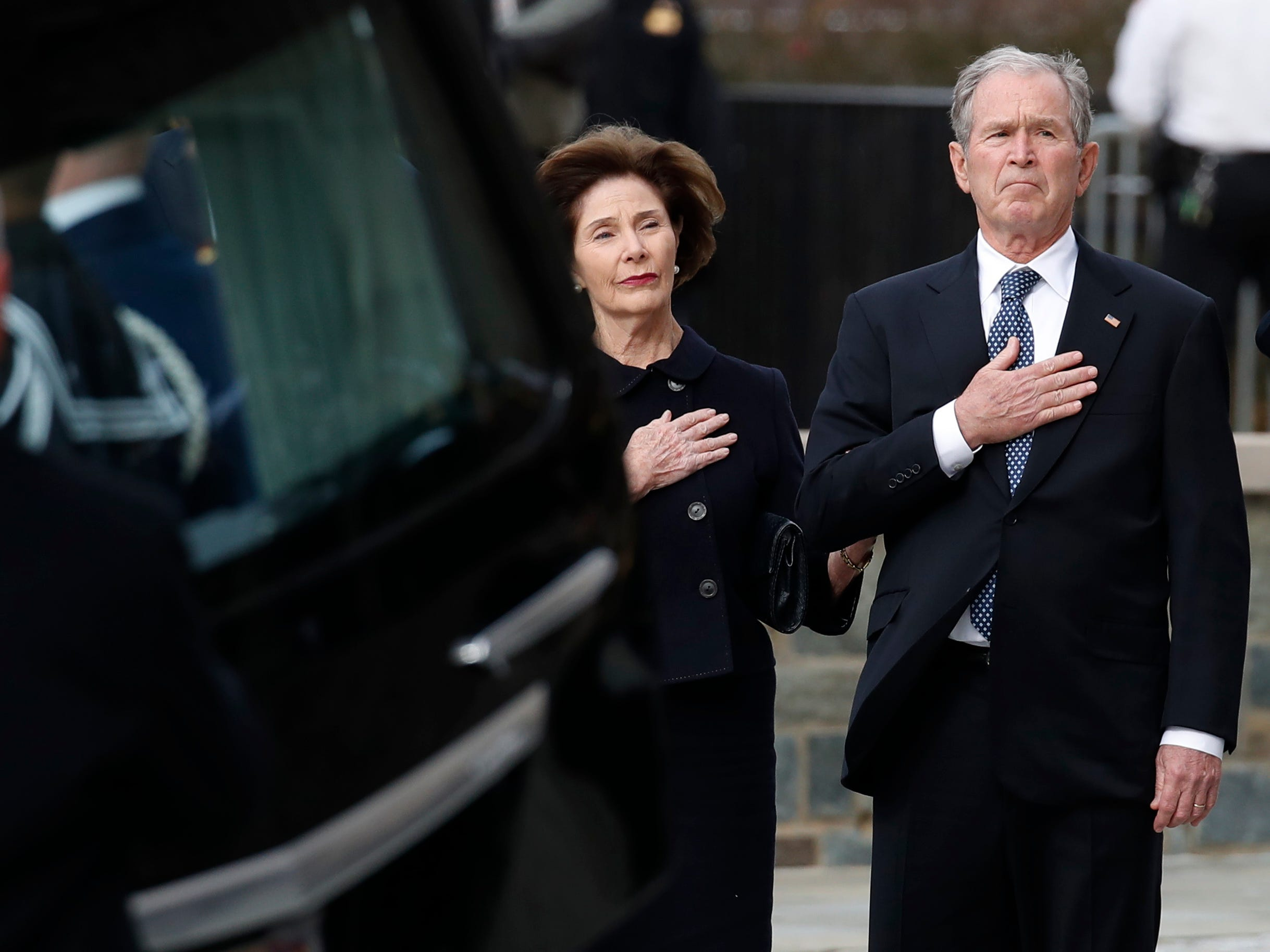 Former President George W. Bush and Laura Bush watch as the flag-draped casket of former President George H.W. Bush is carried by a joint services military honor guard to a State Funeral at the National Cathedral, Wednesday, Dec. 5, 2018, in Washington.