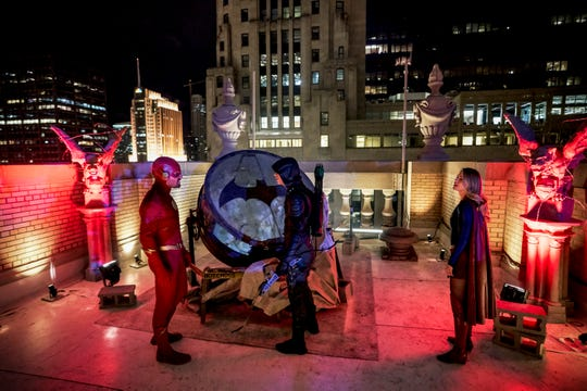 The Flash (Stephen Amell, far left), Green Arrow (Grant Gustin) and Supergirl (Melissa Benoist) get their fill of Gotham City.
