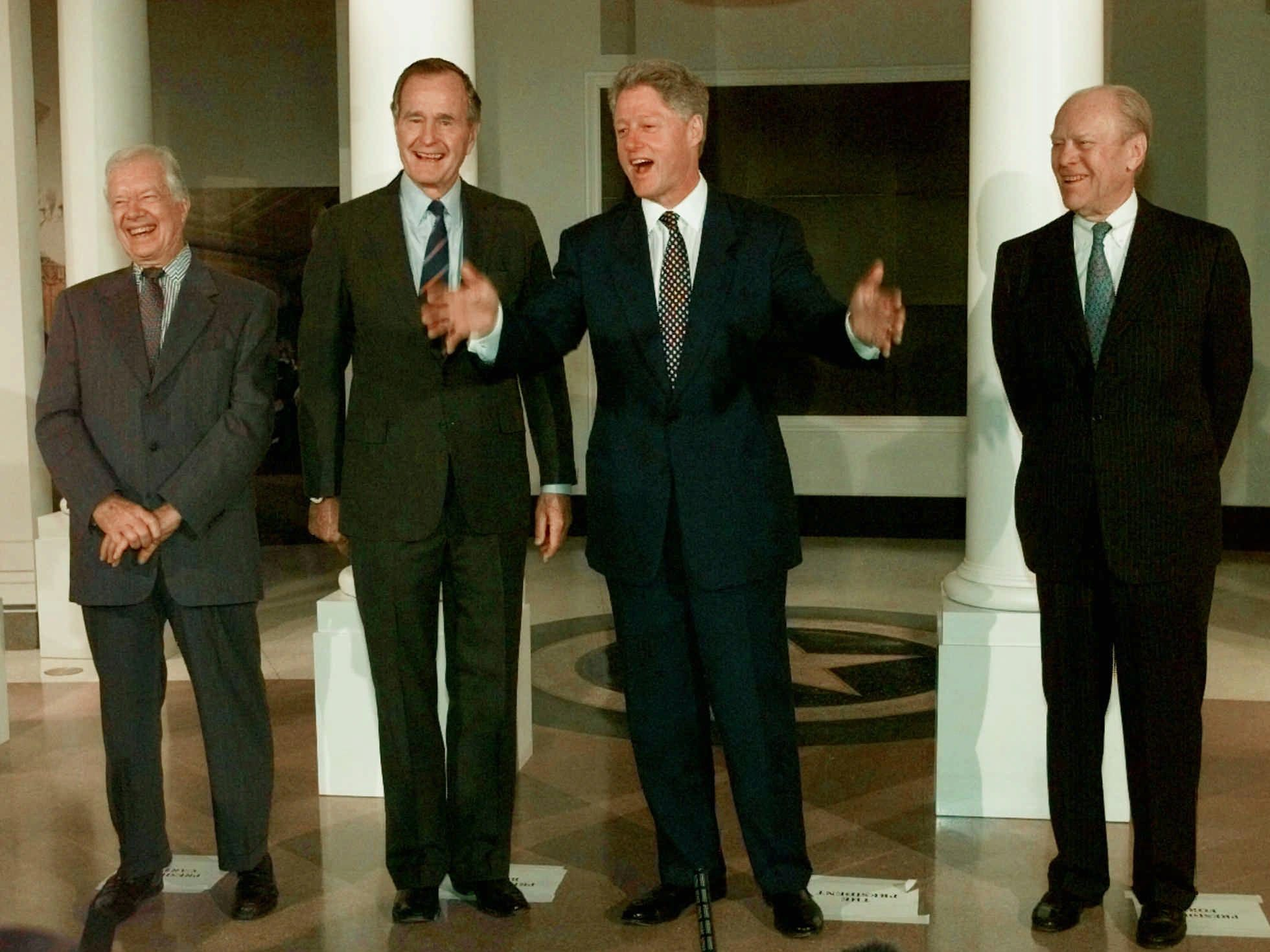 Former Presidents Jimmy Carter, left, George H.W. Bush, and Gerald Ford, right, laugh as President Clinton speaks during a photo session in front of a replica of the White House at the George Bush Presidential Library in College Station, Texas, Thursday, Nov. 6, 1997, prior to the library dedication ceremonies.