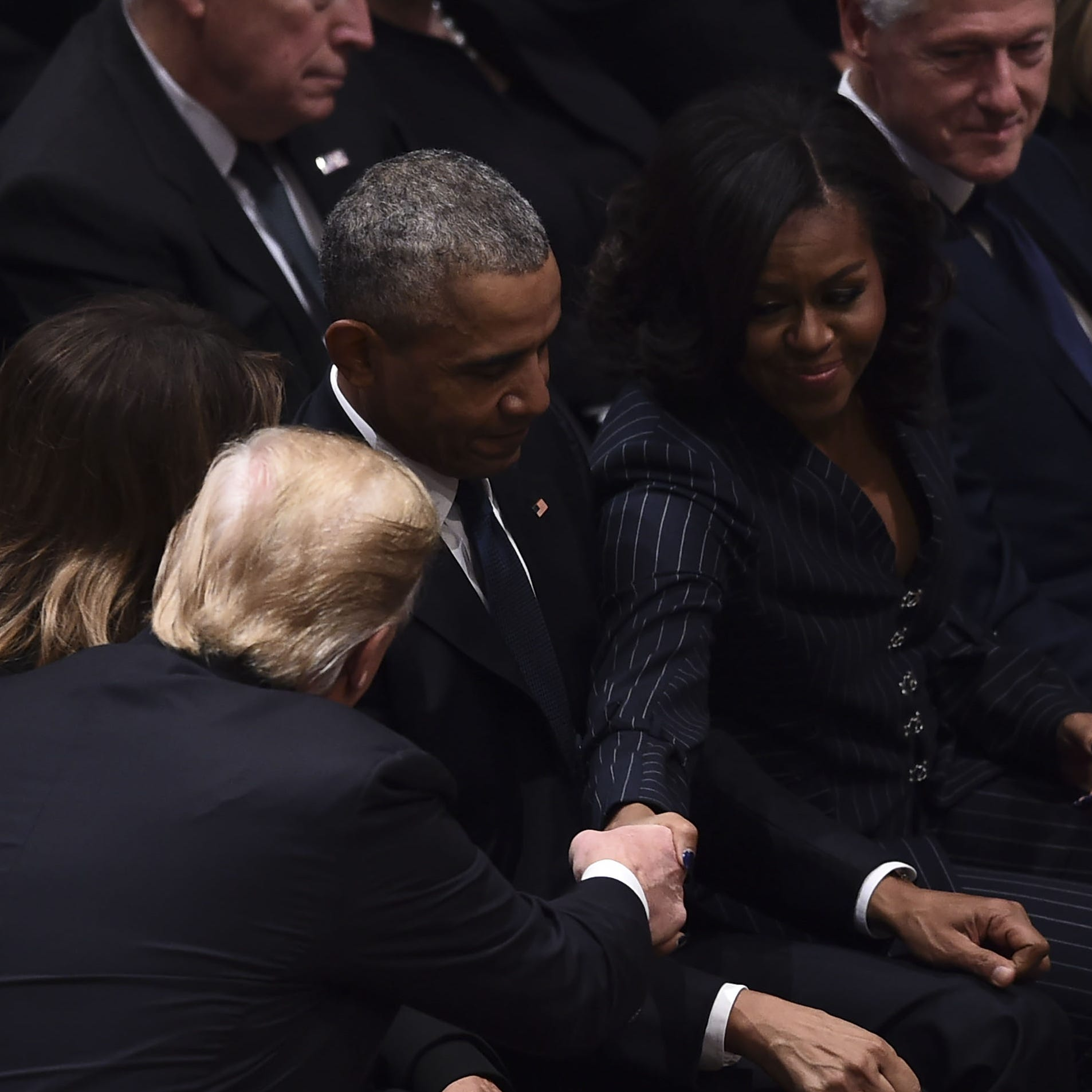 President Donald Trump shakes hands as former President Barack Obama, former first lady Michelle Obama, former President Bill Clinton, former first lady Hillary Clinton, and former President Jimmy Carter sit before the funeral service for former US President George H. W. Bush at the National Cathedral in Washington on Dec. 5, 2018.