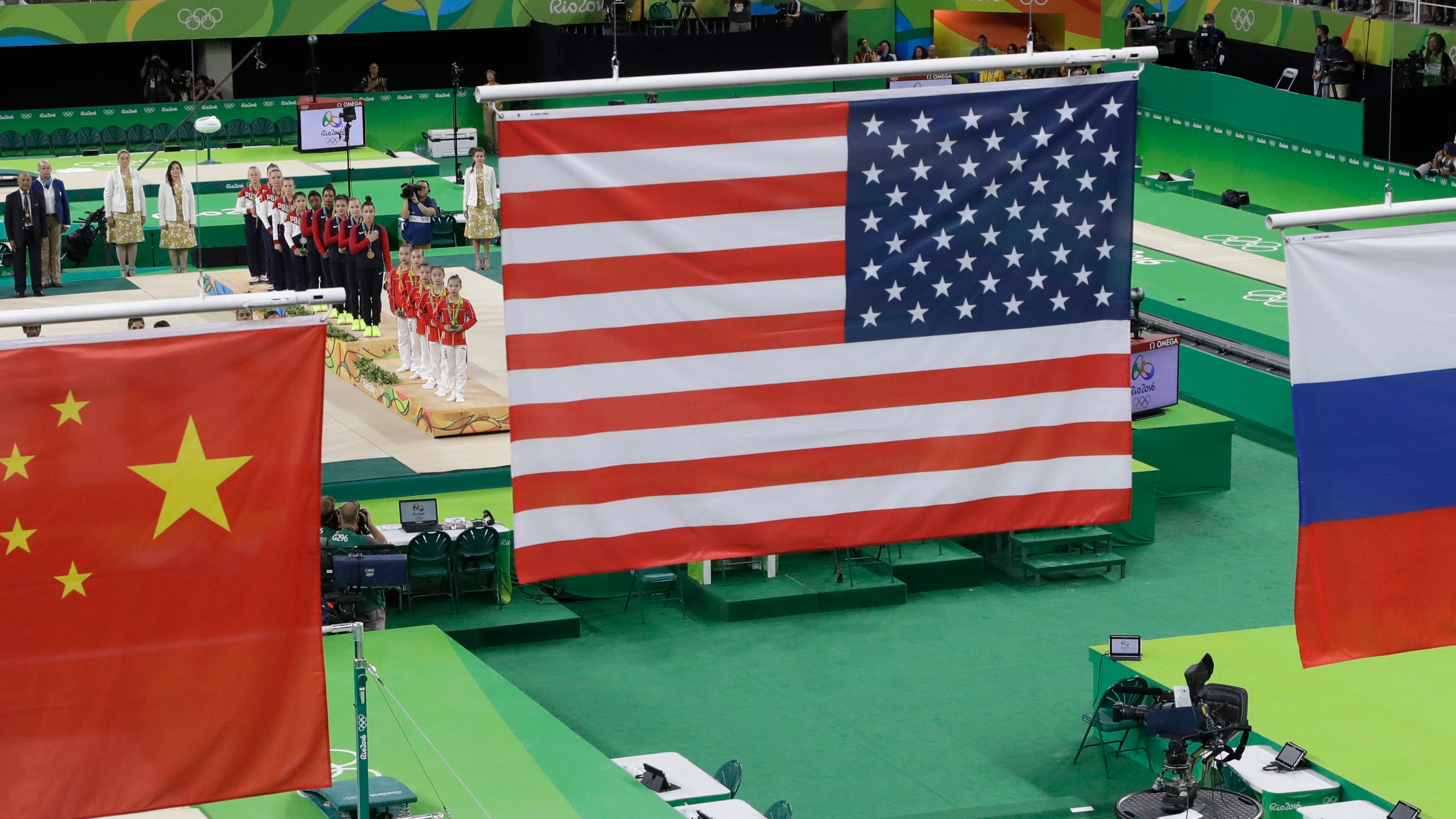 The flags of China, United States and  Russia hang above the gymnasts during the medal ceremony for the women's team event at the 2016 Summer Olympics in Rio de Janeiro.