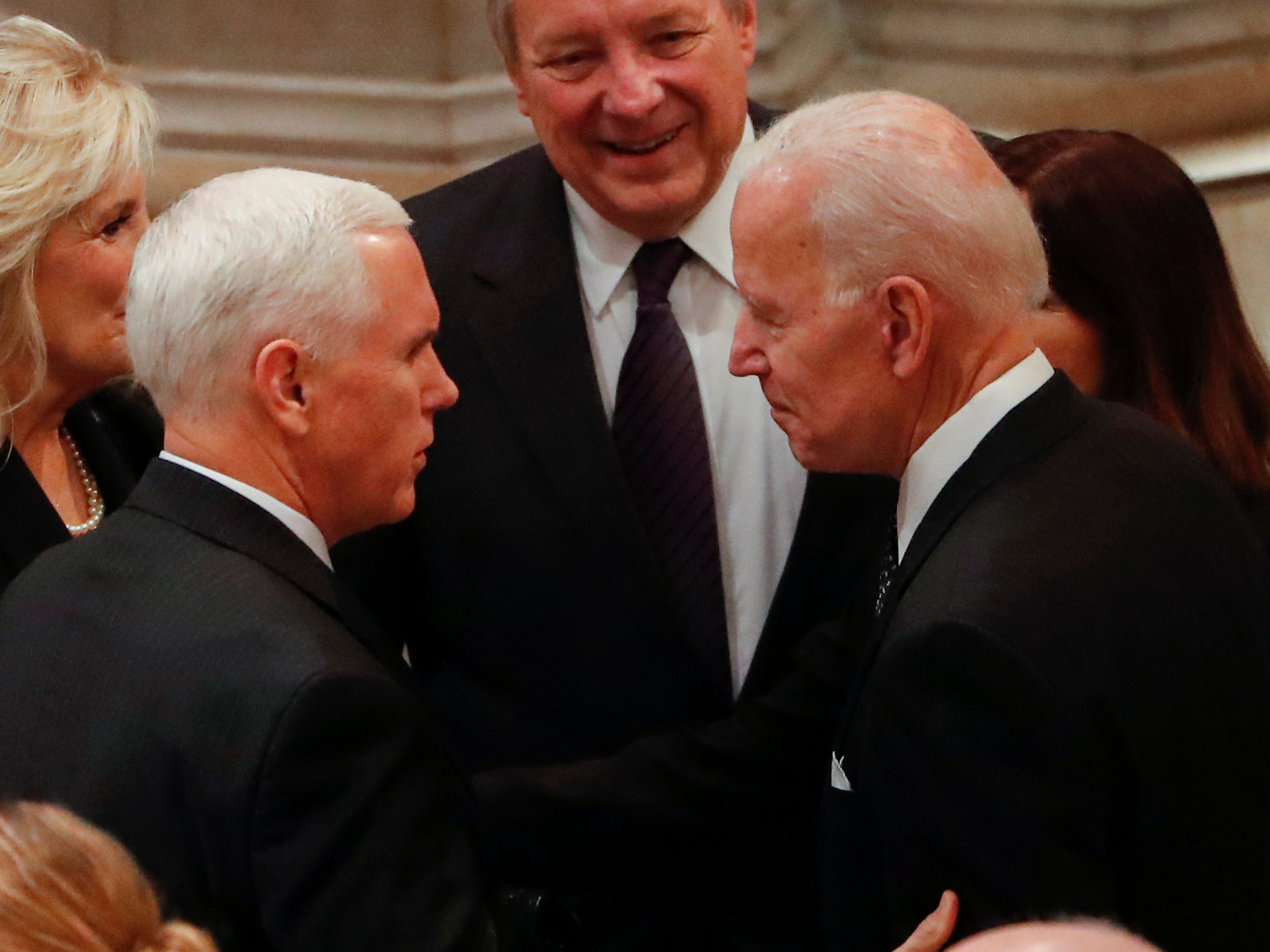 Vice President Mike Pence, left, greets former Vice President Joe Biden as they arrive for the funeral services for former President George H. W. Bush at the National Cathedral, in Washington, Dec. 5, 2018.