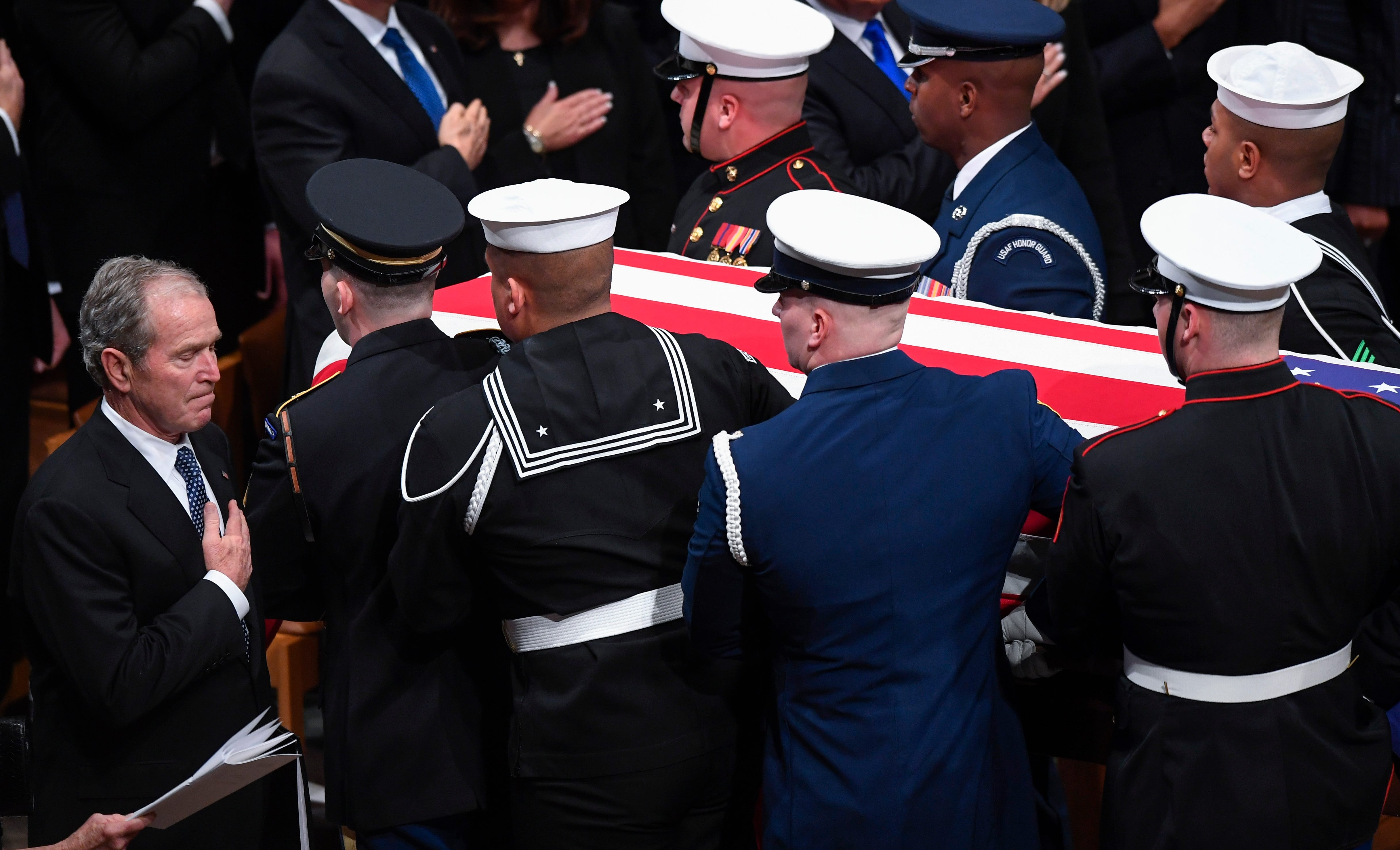 Former President George W. Bush holds his hand on heart as his father and Former President George H.W. Bush is carried from the National Cathedral following being honored with a state funeral at the Washington National Cathedral on Dec. 5, 2018.