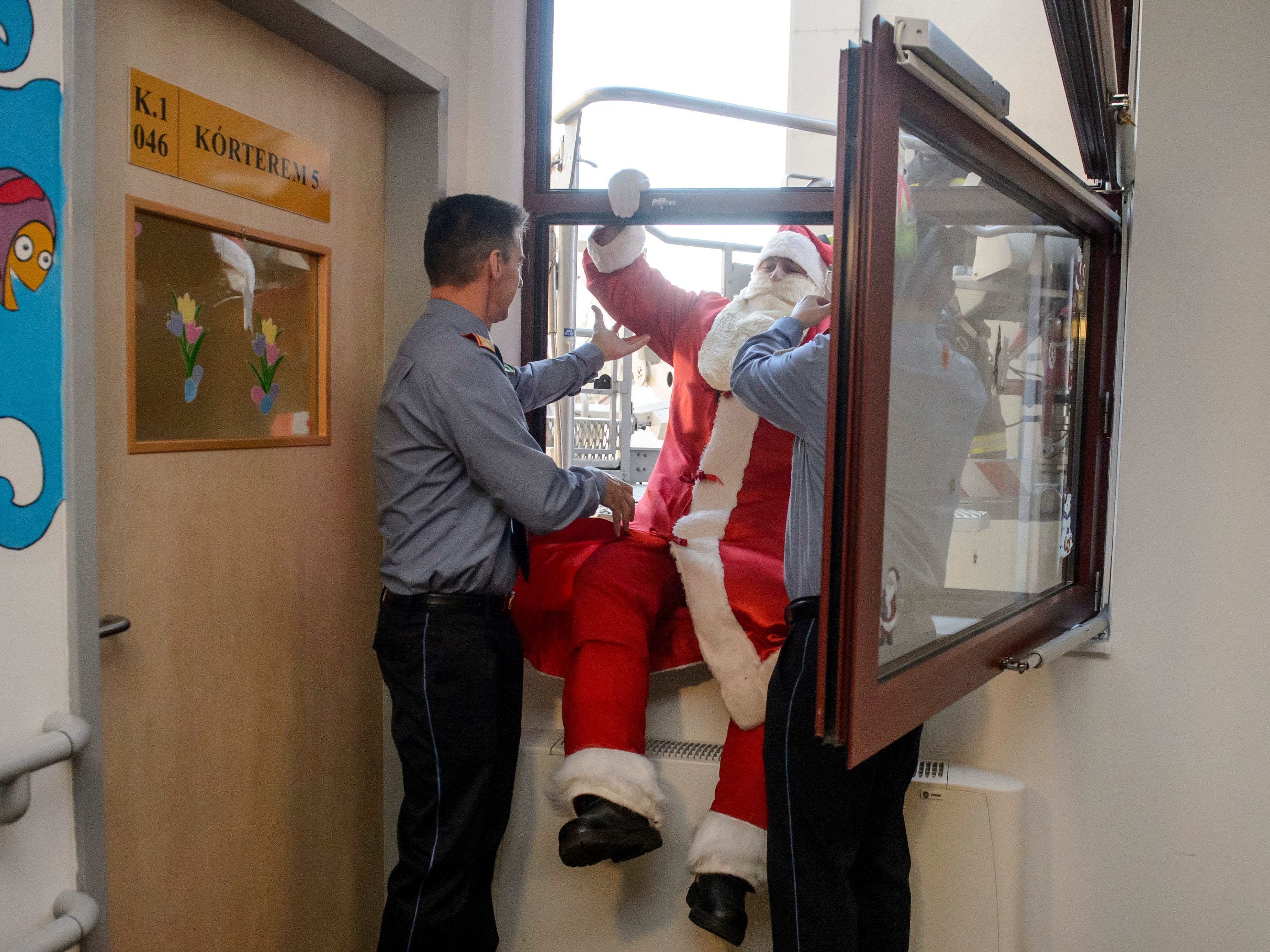 A firefighter dressed as Santa Claus enters through a window into a children's ward from the basket of a fire engine in Markhot Ferenc Hospital in Eger, Hungary, Wednesday, Dec. 5, 2018.