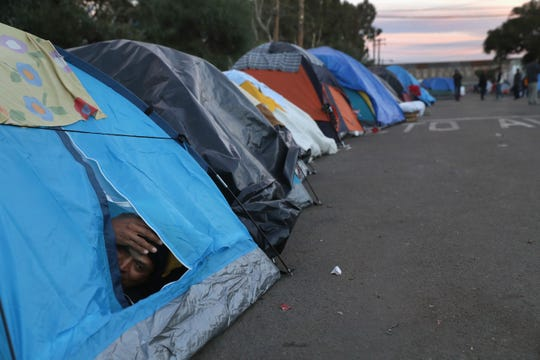 An immigrant awakes while camped out outside a closed migrant camp on Dec. 5, 2018 from Tijuana, Mexico. Hundreds of members of the migrant caravan continue to stay outside the closed camp next to the U.S.-Mexico border fence. After traveling more than 6 weeks from Central America, thousands of immigrants from the migrant caravan remain in Tijuana, many awaiting asylum interviews and others deciding whether to cross illegally into the United States.