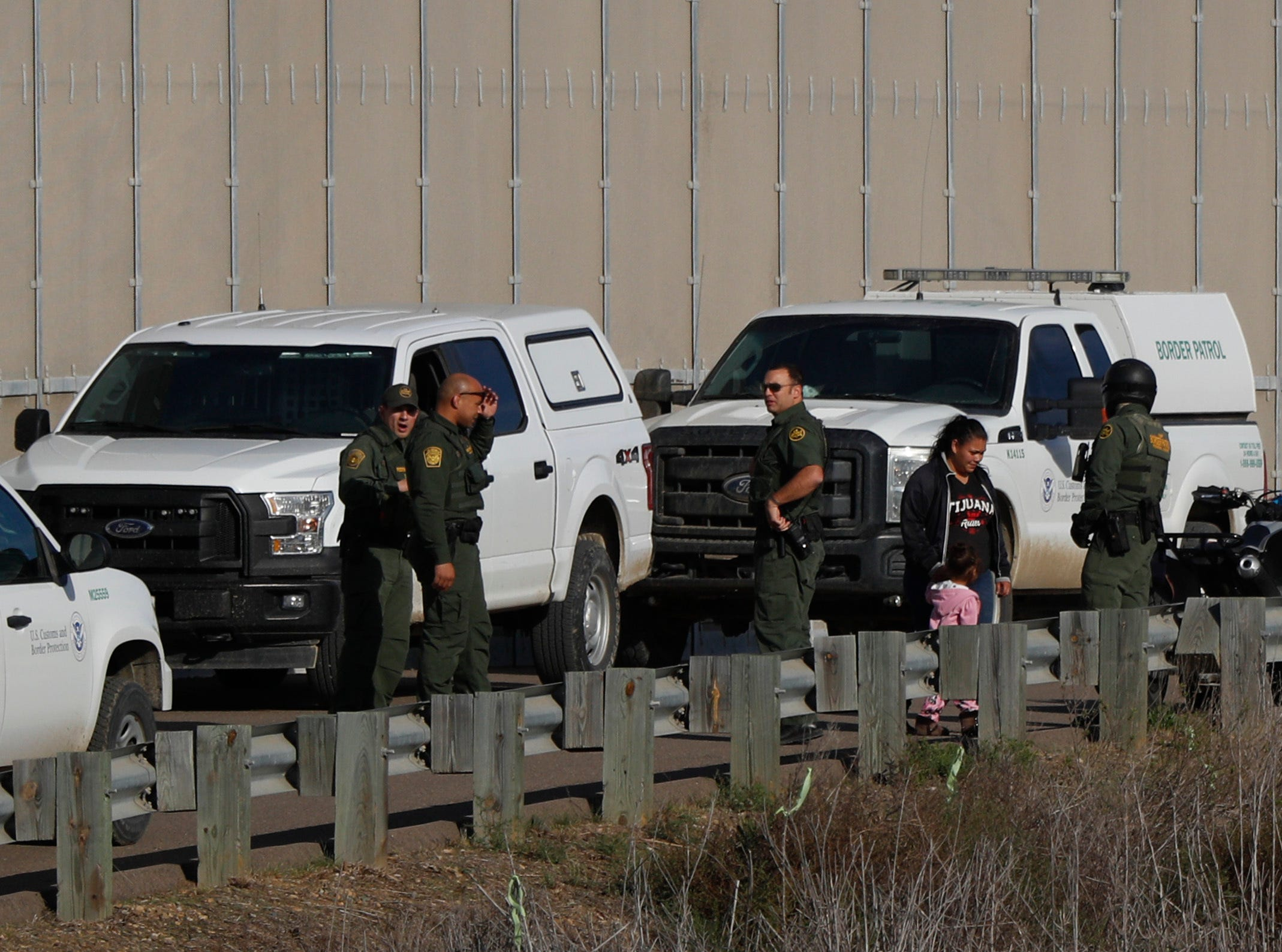 Honduran migrant Rachel Rivera, 19, and her 3-year-old daughter Charlot Andrea are detained by U.S. border patrol after they crossed under the U.S. border wall from Playas de Tijuana, Mexico, Tuesday, Dec. 4, 2018. Weeping as she stayed behind in Tijuana with her Mexican husband, Rivera's mother Yesenia said her daughter and granddaughter had joined the migrant caravan to flee an abusive husband back in Honduras.