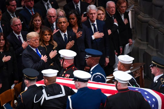 President Donald Trump and First Lady Melanie Trump with former President Barack Obama and Michelle Obama, former President Bill Clinton and former Secretary of State Hillary Clinton, and former President Jimmy Carter and Rosalynn Carter, watch the conclusion of the State Funeral for former President George H.W. Bush at the Washington National Cathedral in Washington, Dec. 5, 2018.