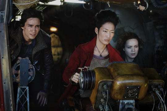 "Tom Natsworthy (Robert Sheehan, left), Anna Fang (Jihae) and Hester Shaw (Hera Hilmar) lead the good guys into battle in the epic ""Mortal Engines."""
