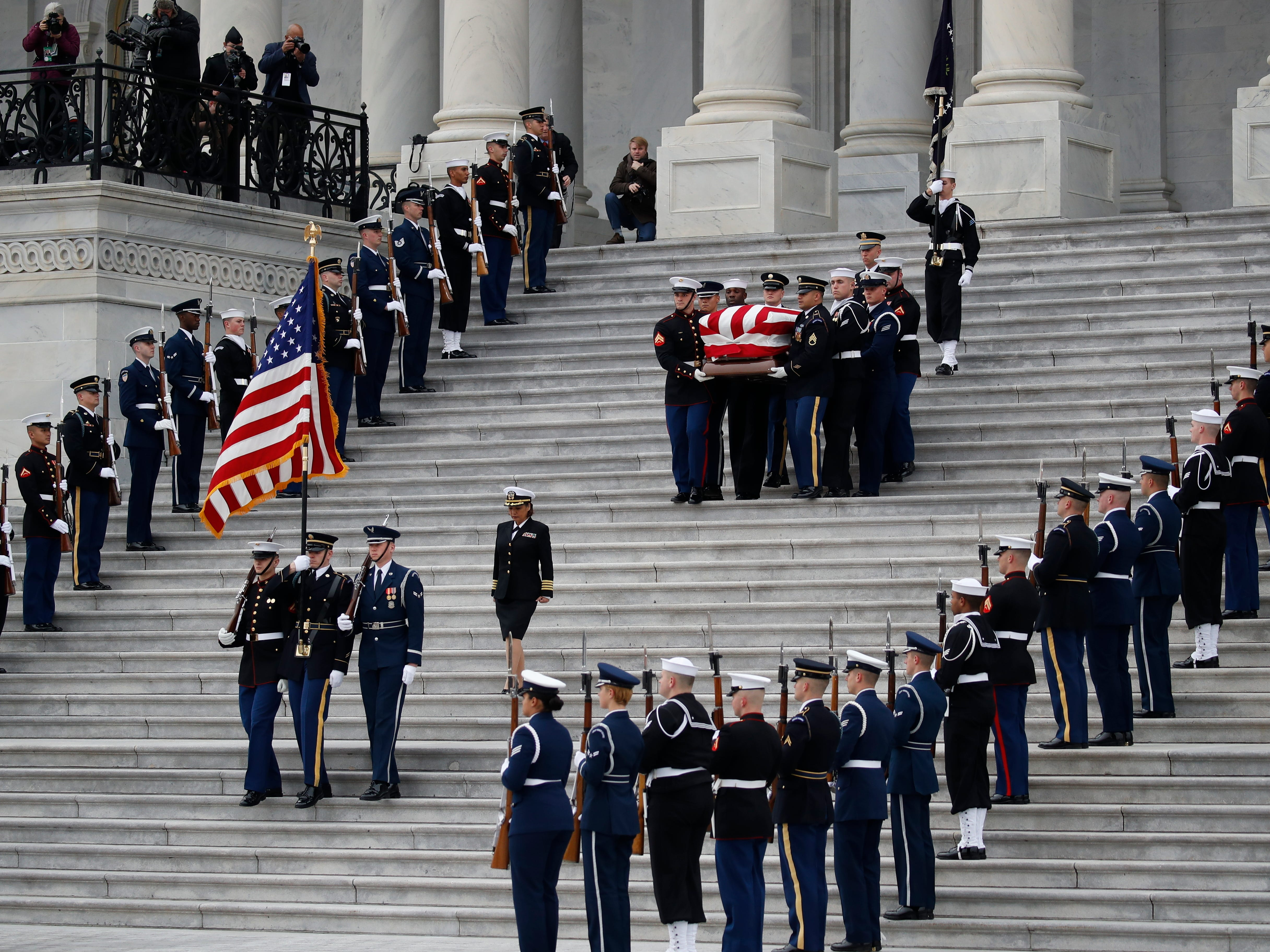 The flag-draped casket of former President George H.W. Bush is carried by a joint services military honor guard from the U.S. Capitol, Wednesday, Dec. 5, 2018, in Washington.