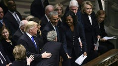 Former president George W. Bush (C), flanked by his wife Laura (bottom L)  reaches past (from L-R) US President Donald Trump, First Lady Melania and former president Barack Obama to give former first Lady Michelle Obama something as US president Bill Clinton and Hillary Clinton, and former president Jimmy Carter and Rosalynn Carter look on during the funeral service former president George H.W.Bush at the Washington National Cathedral in Washington, D.C.