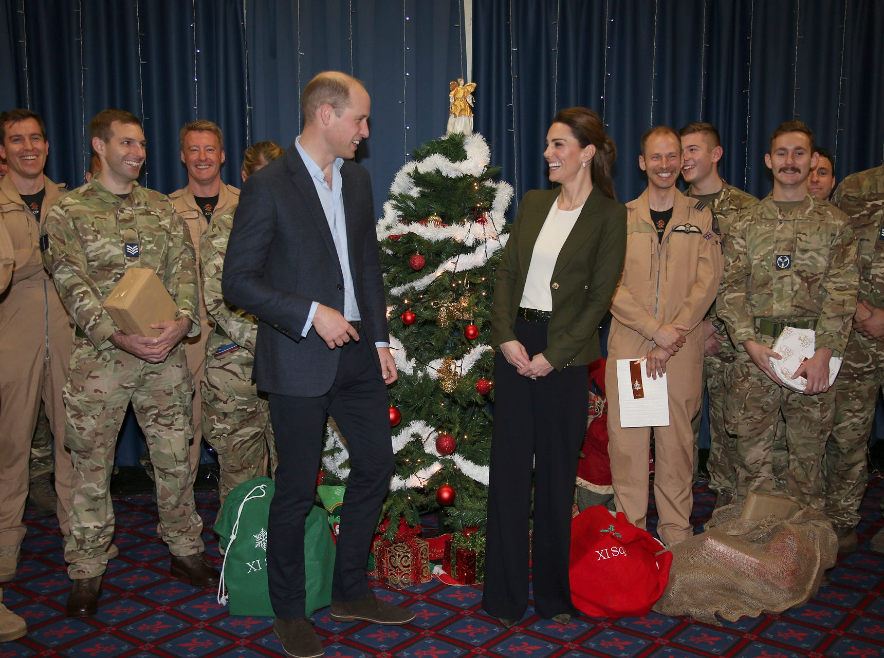 Prince William and Kate Duchess of Cambridge pose with Service Personnel during a Christmas party on RAF Akrotiri in Cyprus, as the Royal couple visit the Sergent's mess to hand out gifts Wednesday Dec. 5, 2018.  The RAF Akrotiri is the home of the Cyprus Operations Support Unit which supplies support to operations in the region to protect the UK's strategic interests. (Ian Vogler/Pool via AP) ORG XMIT: LON824