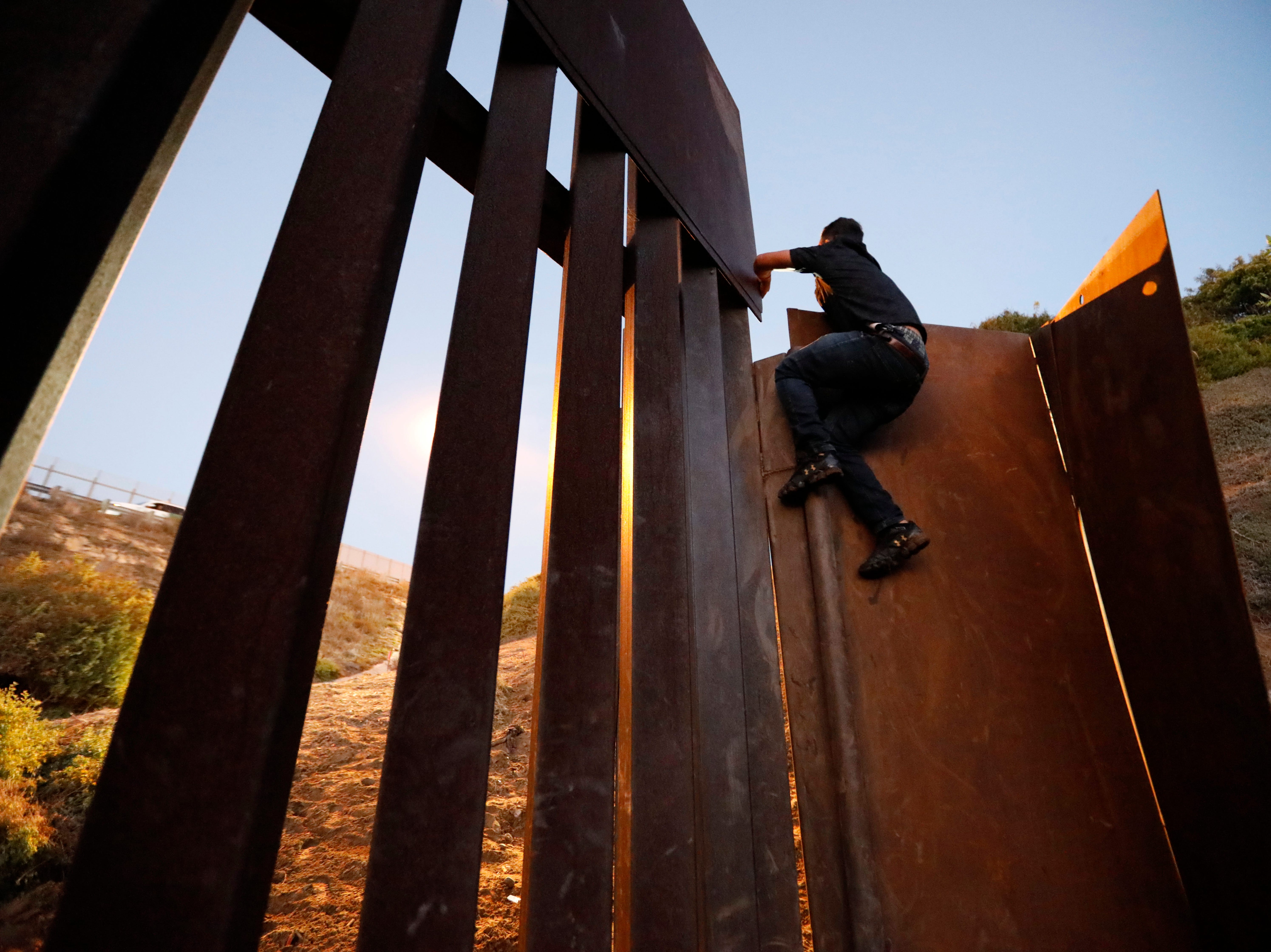 A man pulls himself up onto the U.S. border wall as he and other migrants climb over to San Ysidro, Calif., in order to surrender to the U.S. Border Patrol, in Playas de Tijuana, Mexico, Monday, Dec. 3, 2018.