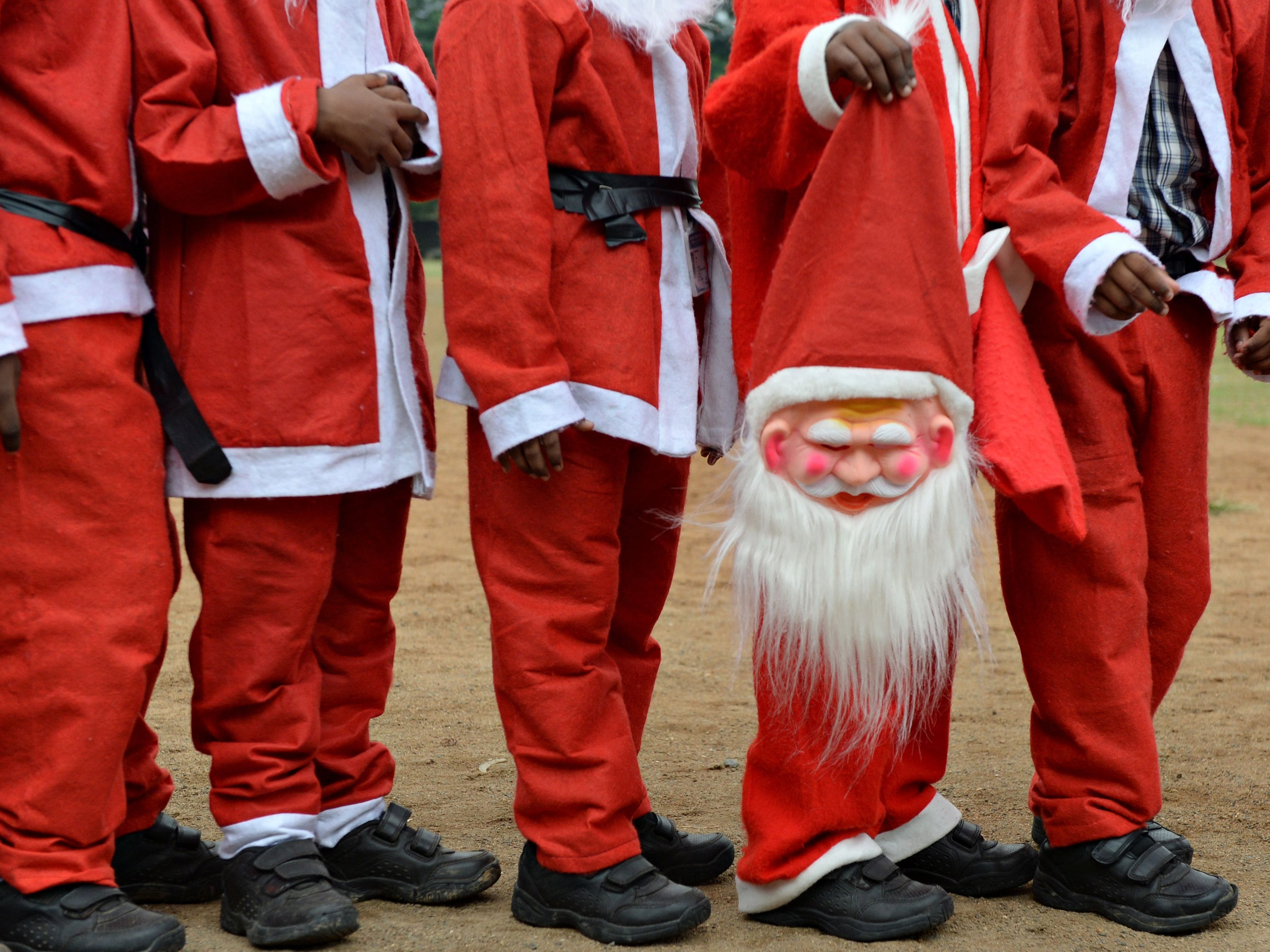 Indian schoolchildren dressed as Santa Claus pose as they take part in a Christmas event at a school in Chennai, India,  Dec. 5, 2018.
