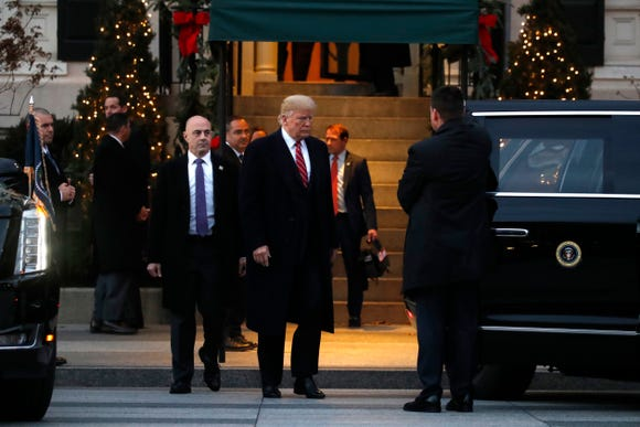 After walking first lady Melania Trump to her side of the vehicle, President Donald Trump walks to the other side of the vehicle as they leave Blair House after visiting with the family of former President George H. W. Bush, Dec. 4, 2018, in Washington.