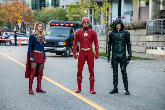 """Supergirl (Melissa Benoist, left), the Flash (Stephen Amell) and Green Arrow  (Grant Gustin) stand tall as the """"Arrowverse's"""" heroic trinity."""