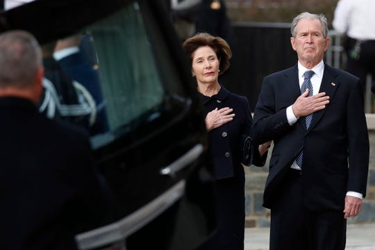 Former President George W. Bush and former first lady Laura Bush watch as the flag-draped casket of former President George H.W. Bush is carried by a joint services military honor guard to a State Funeral at the National Cathedral, in Washington, DC, on Dec. 5, 2018.