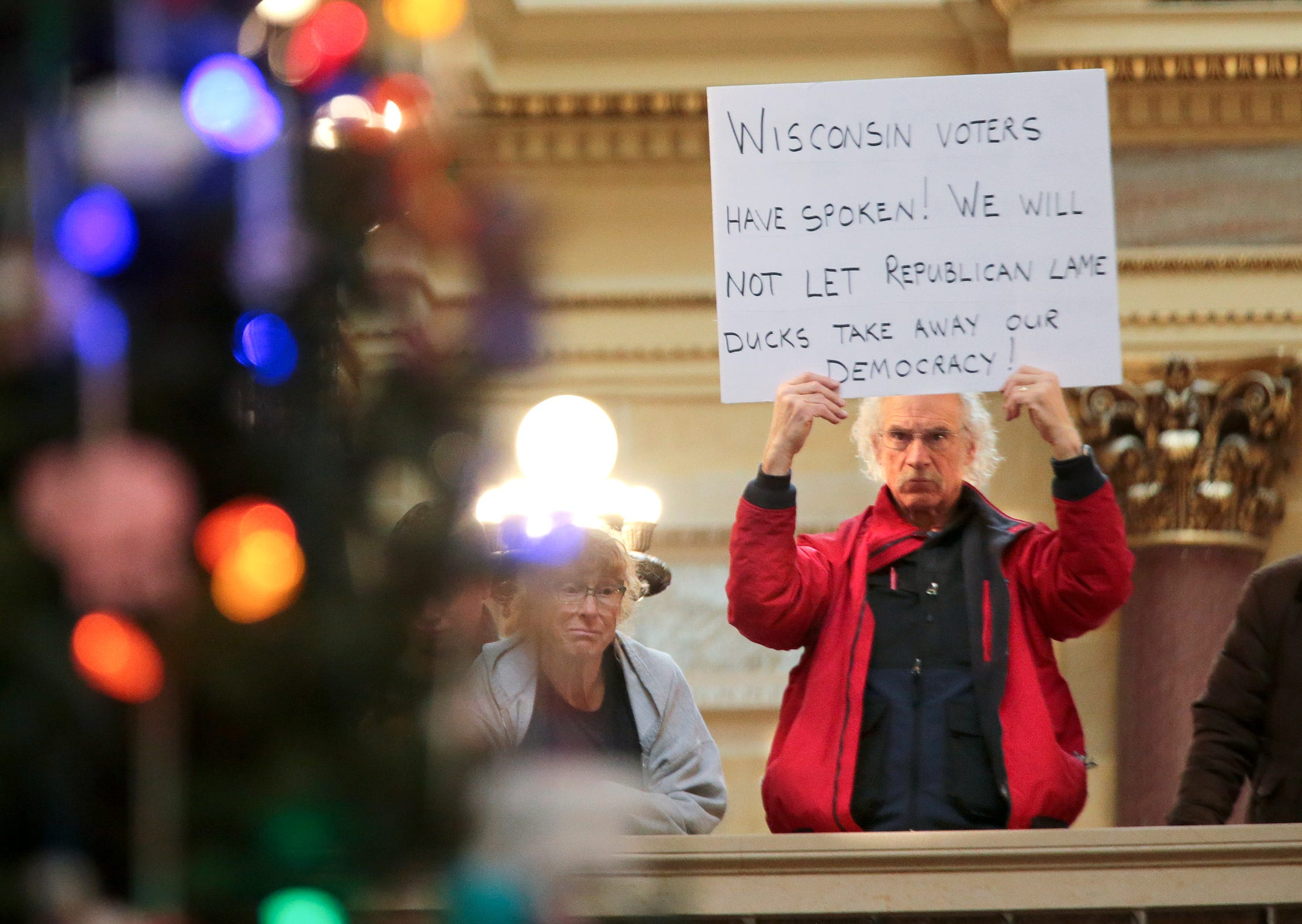 Bob Kinosian, from Wauwatosa, Wis., holds up a sign during the state Christmas Tree lighting ceremony in state Capitol Rotunda on Dec. 4, 2018, in Madison, Wis.