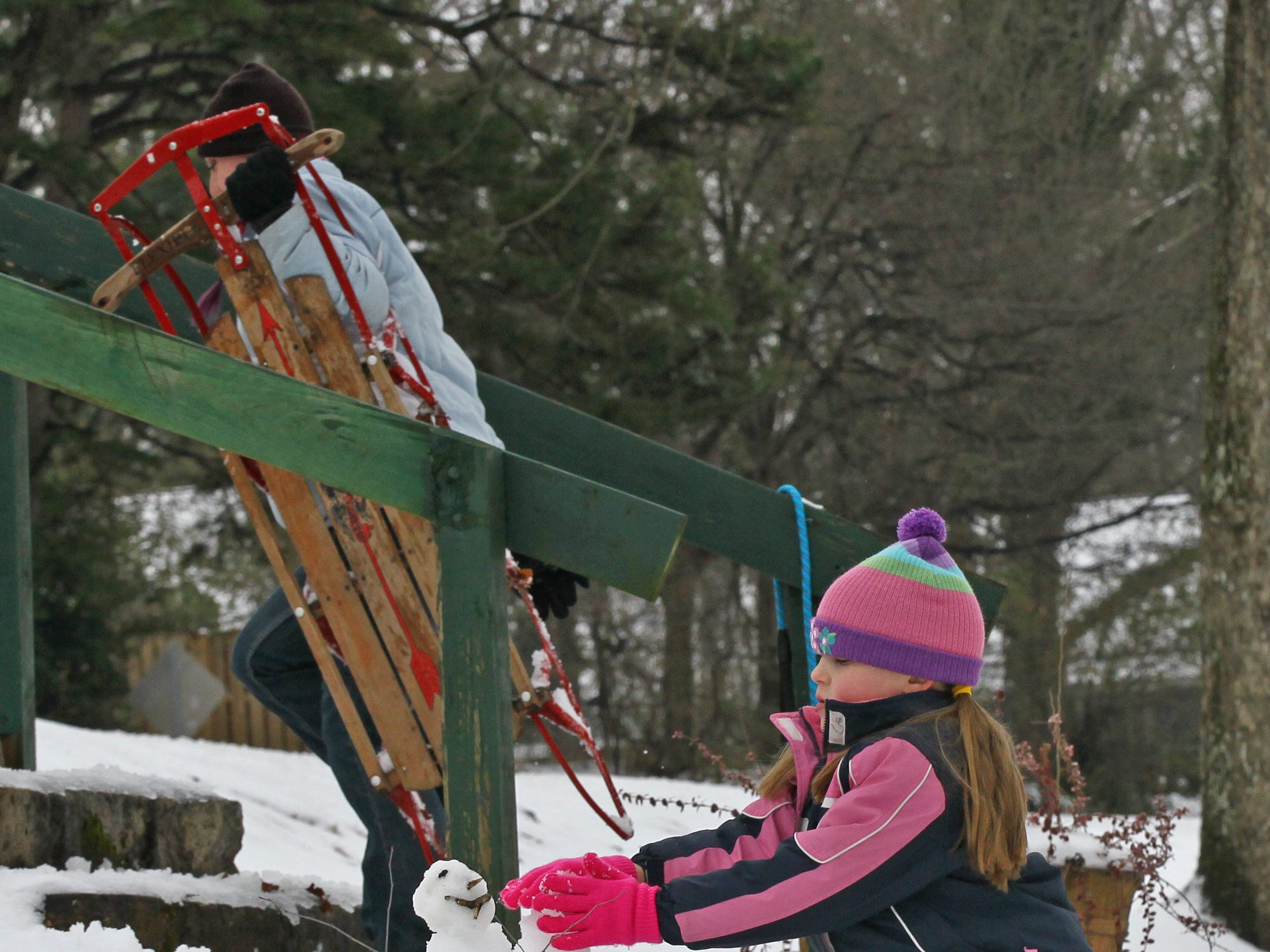 Faith Stansell of Anderson builds a snowman while other sled down hills at Linley Park in Andersonduring the first snow of 2014.