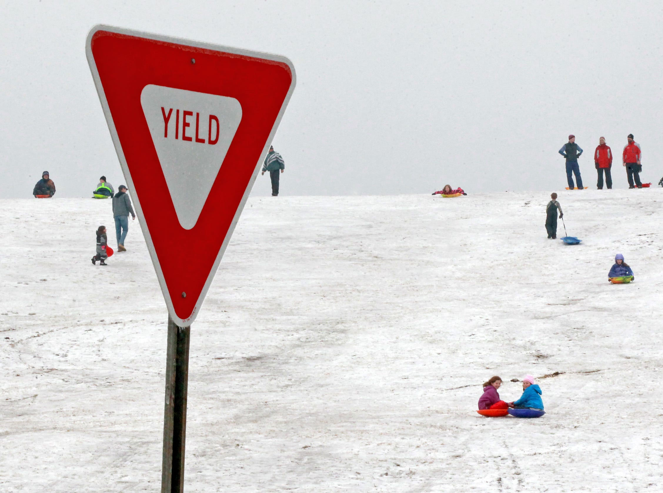 Parents and children slide down a snow-covered Kite Hill off of U.S. 76 in Clemson in 2015.