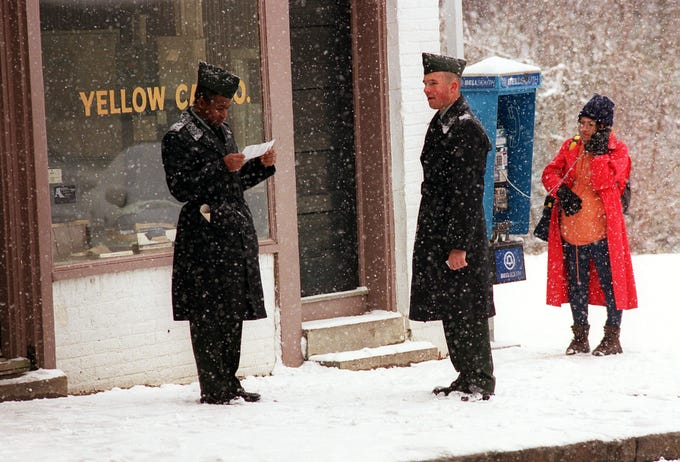U.S. Army private Andy Goodwin, left, of Anderson, S.C. looks at his Greyhound Bus ticket in the snow while fellow U.S. Army private Kenneth McGlotten, of Belton, S.C., and Lily Mattern of Anderson, S.C. wait for a ride home after the finding out the bus from Charlotte, N.C. to Atlanta, Ga., stopping through Anderson, S.C., was cancelled Thursday January 3, 2002.
